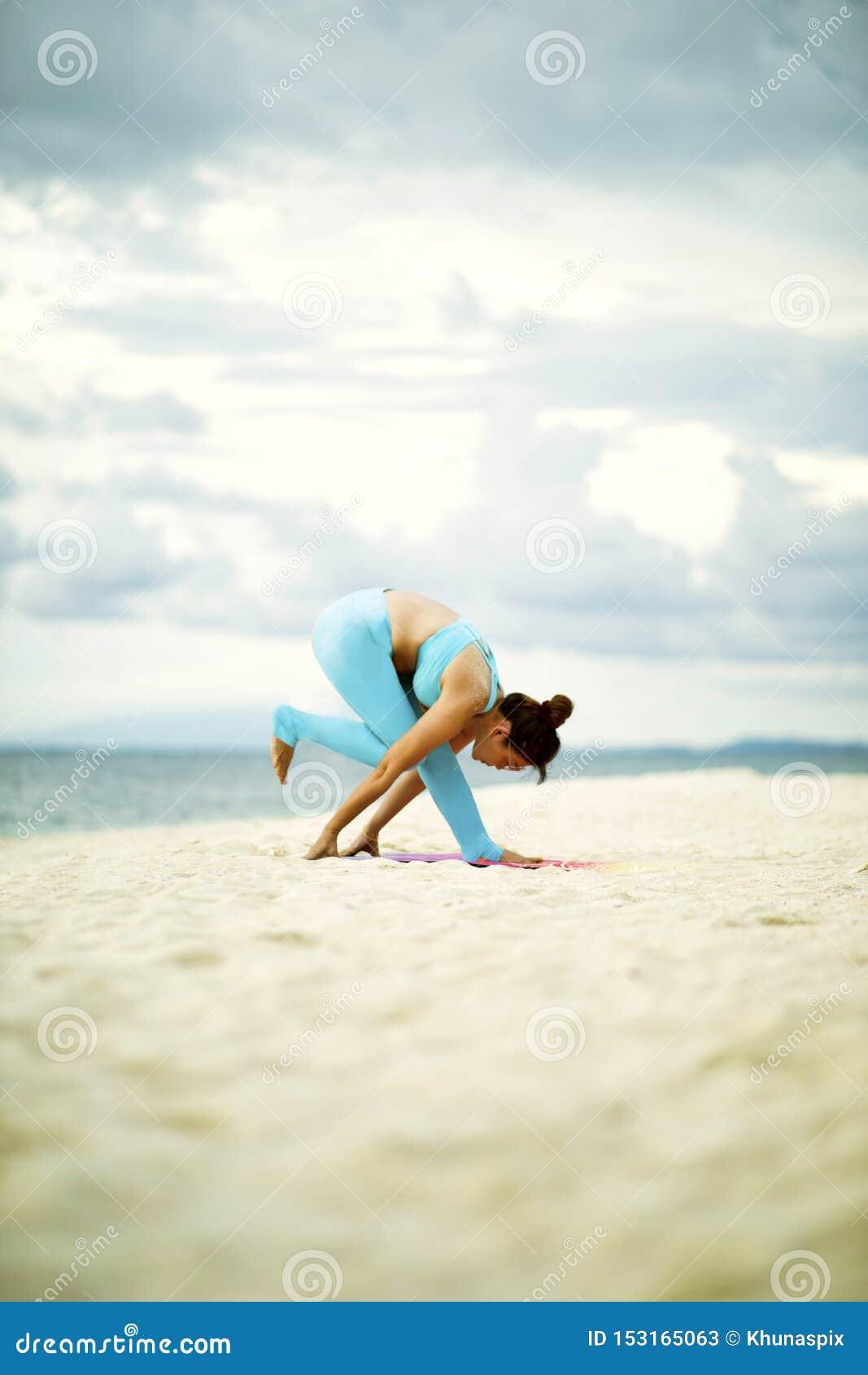 Mujer que juega actitud de la yoga en la playa de la arena