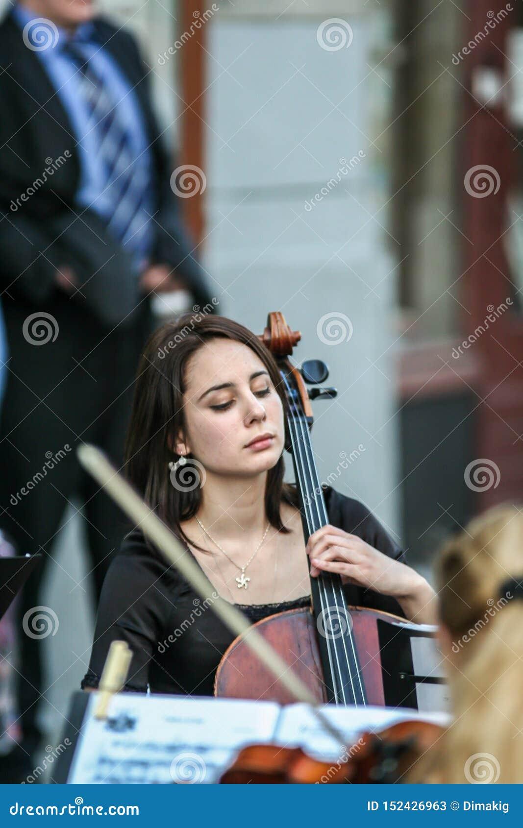 Mujer que juega en la calle, vista lateral del violoncelista