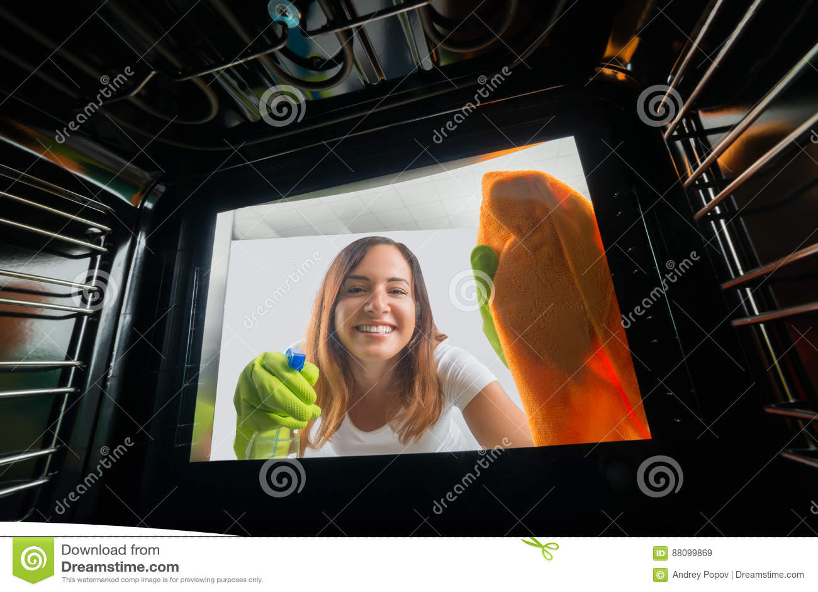 Mujer Que Limpia La Puerta De Cristal Del Horno Imagen De Archivo  ~ Como Limpiar El Cristal Del Horno