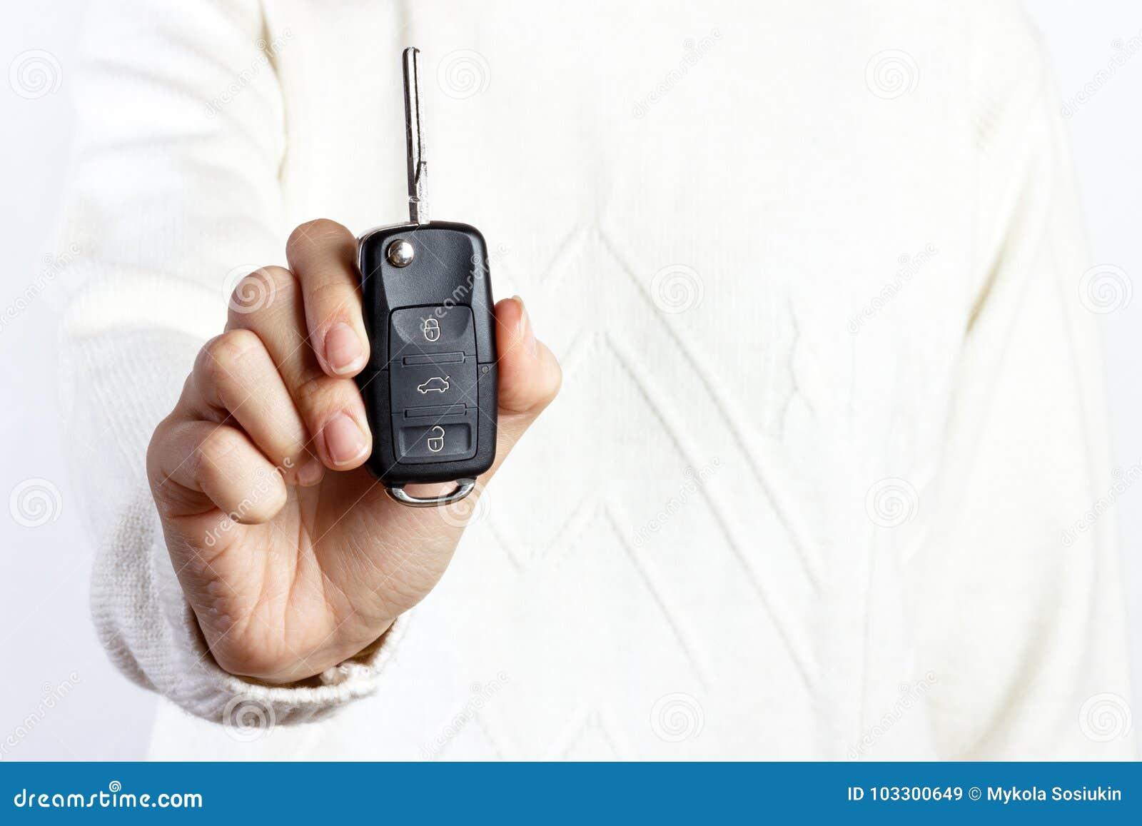 Mujer que lleva a cabo una llave del coche en los fondos blancos