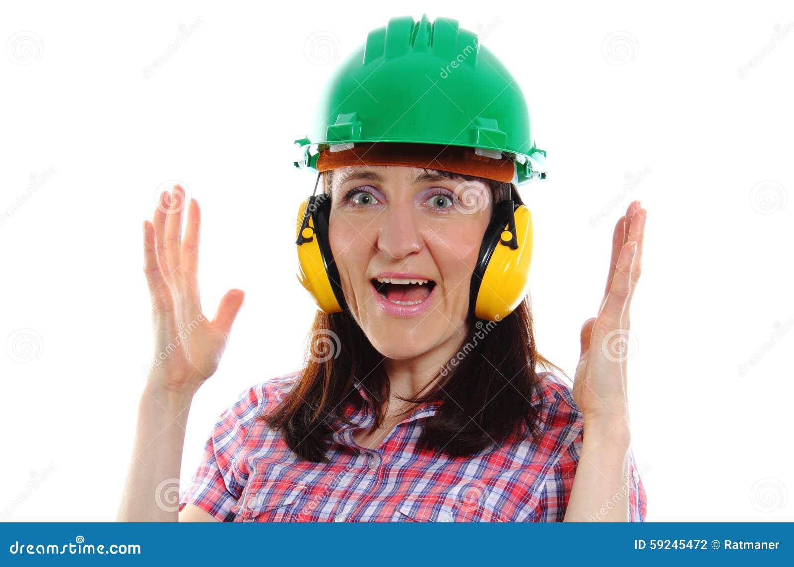 Mujer que lleva el casco y los auriculares protectores