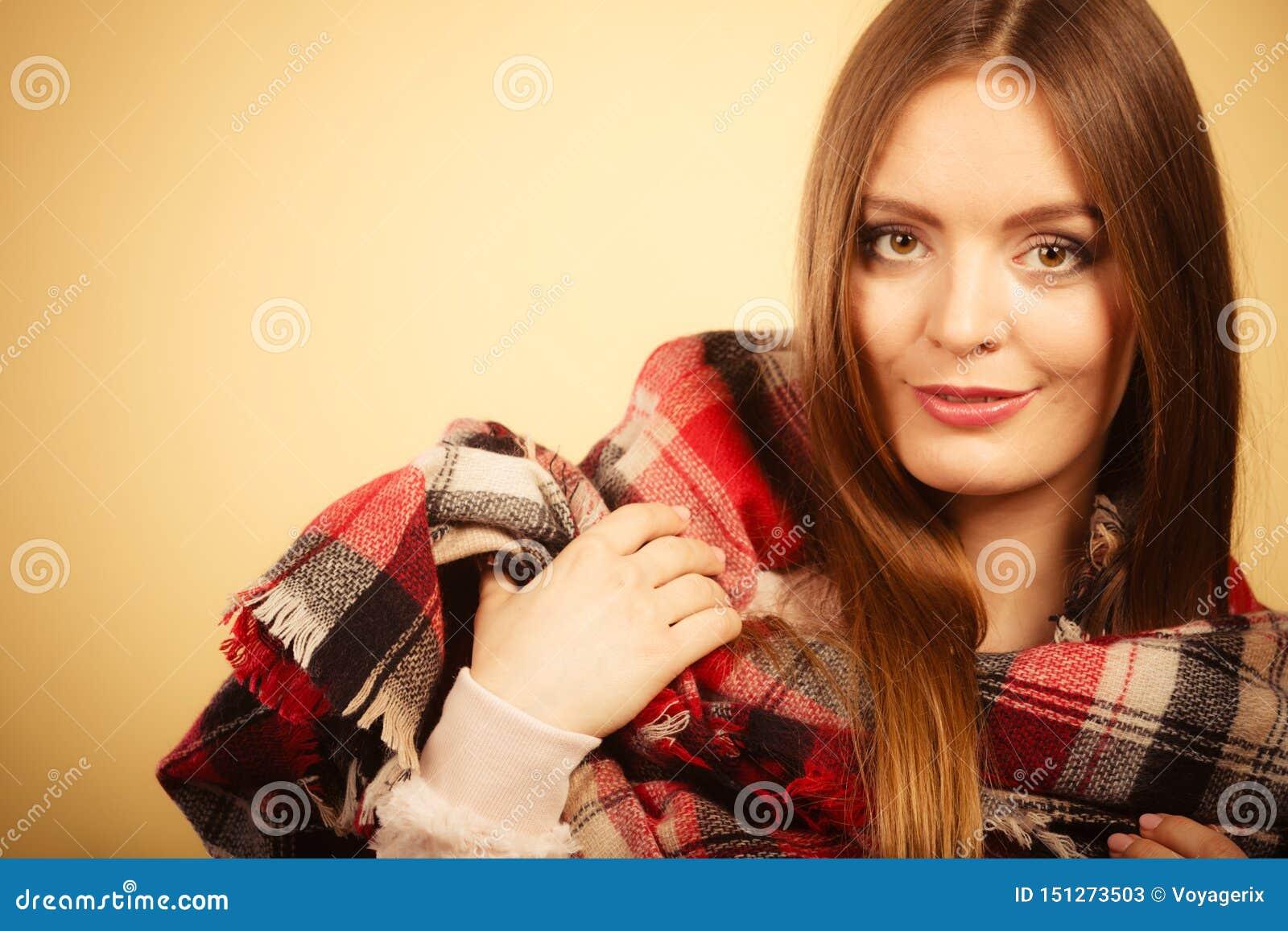 Mujer que lleva la ropa caliente comprobada de lana del oto?o de la bufanda