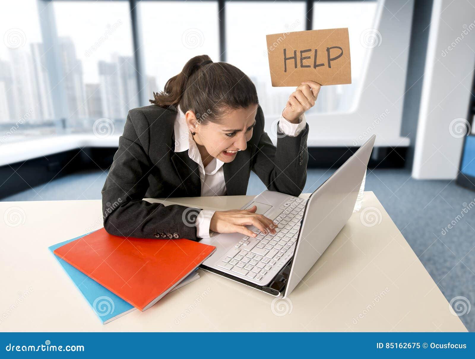 Mujer que lleva un traje de negocios que trabaja en su ordenador portátil que lleva a cabo una muestra de la ayuda que se sienta
