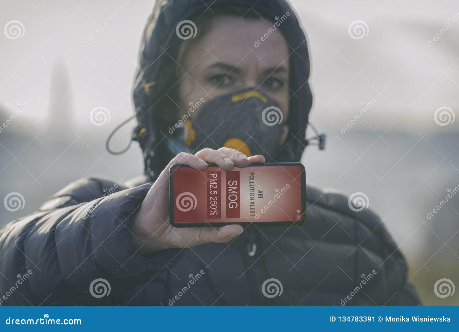 Mujer que lleva una mascarilla contra la niebla real y que comprueba la contaminación atmosférica actual con el app elegante del