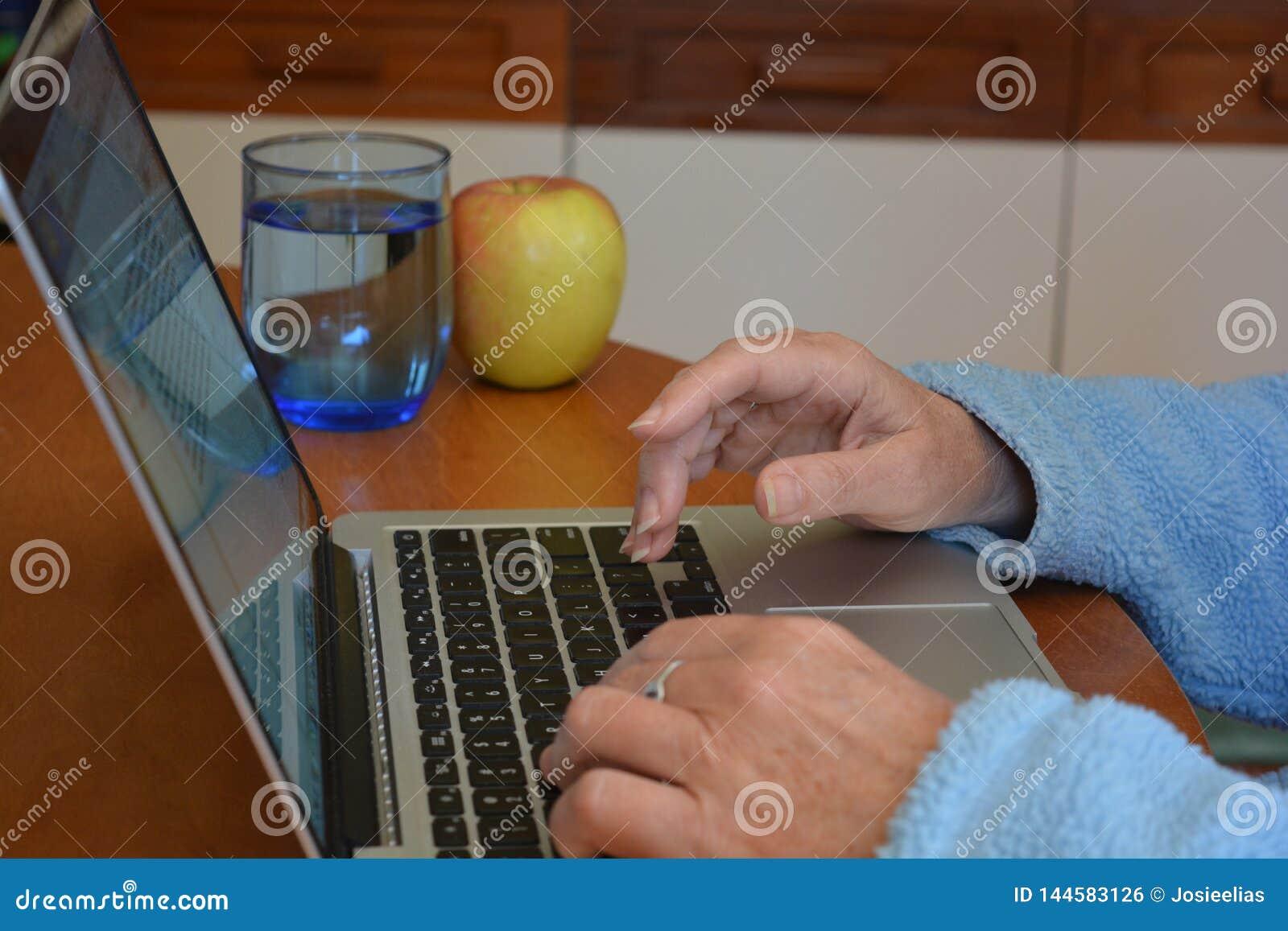 Mujer que mecanografía en el teclado del ordenador portátil, cierre para arriba