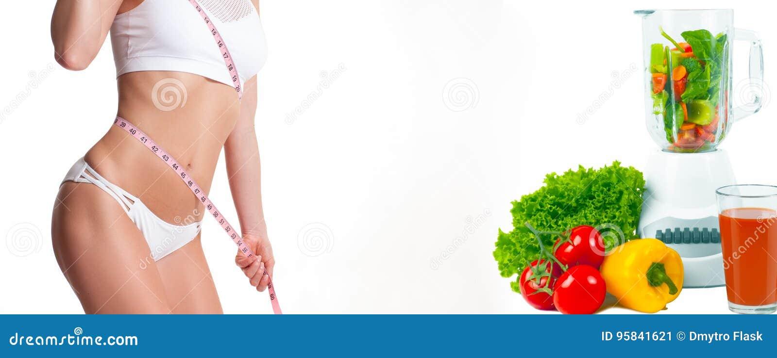 Mujer que mide su cuerpo con una cinta de la medida Concepto de la dieta, verduras frescas