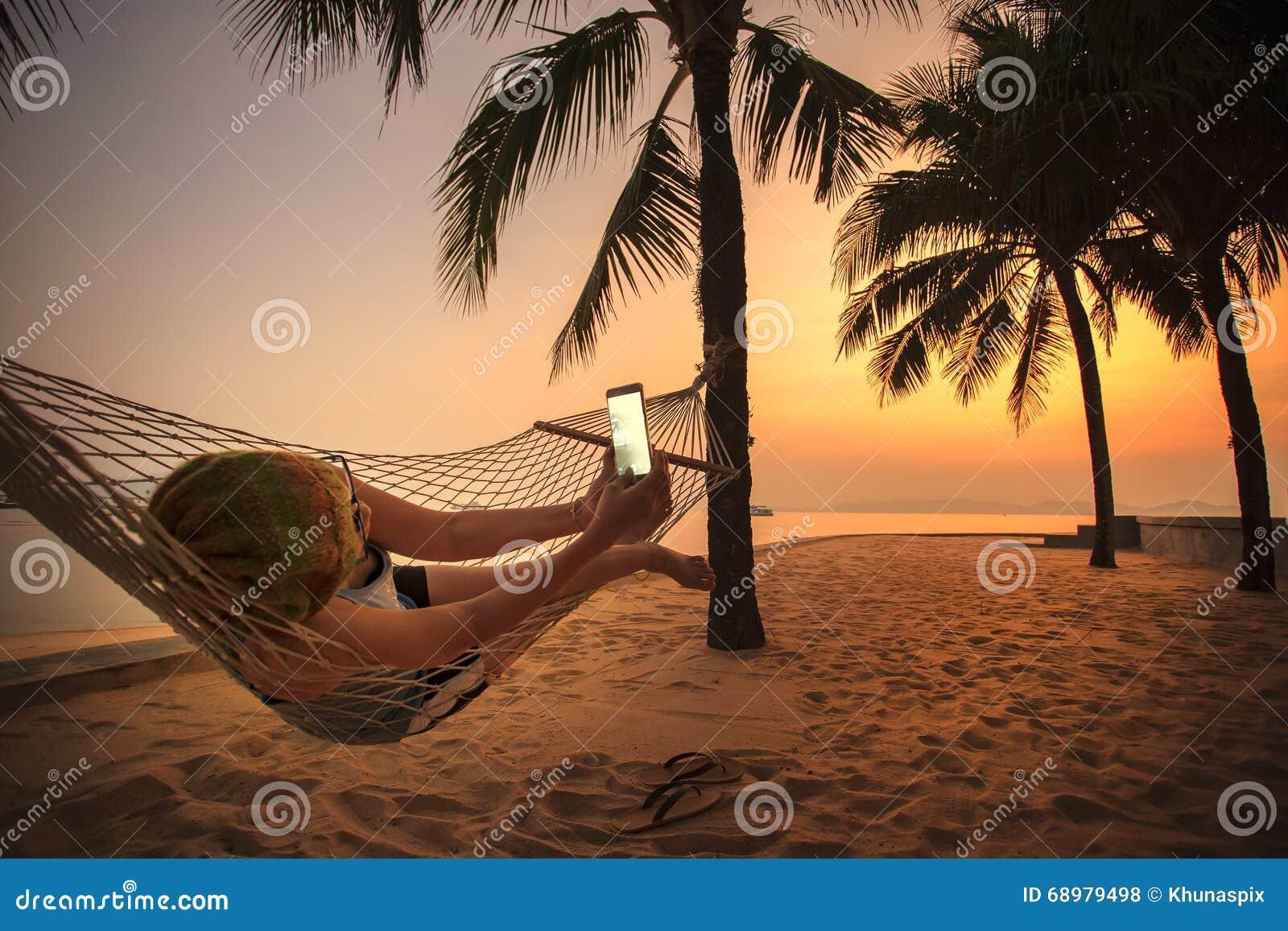 Mujer que miente en cuna de la playa y que toma una fotografía por pho elegante