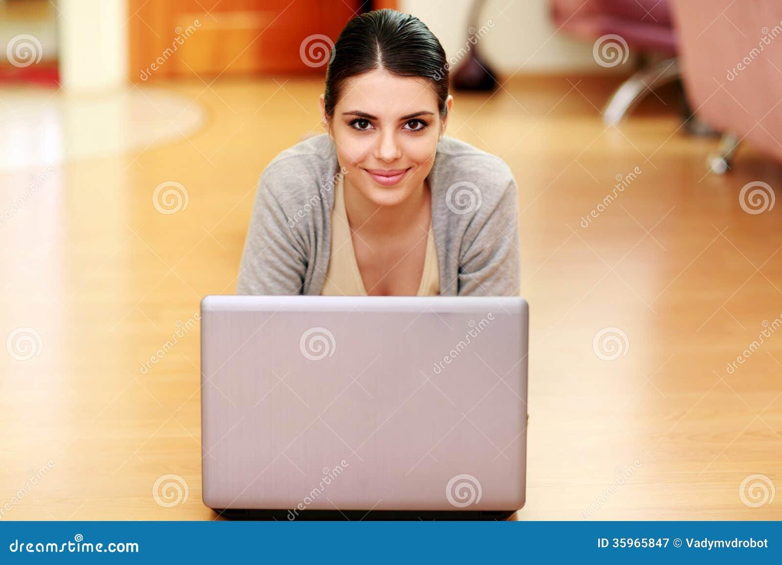 Mujer que miente en el piso con el ordenador portátil