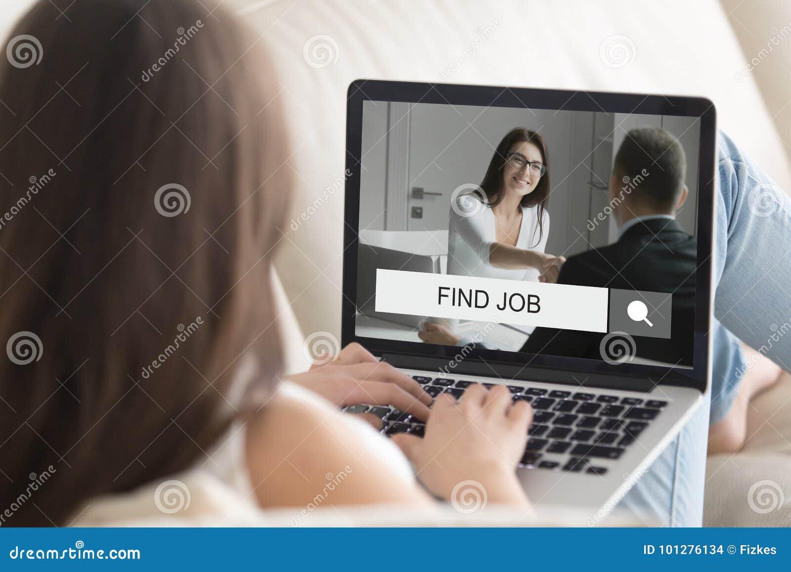 Mujer que miente en el sofá con el ordenador portátil, intentando encontrar trabajo