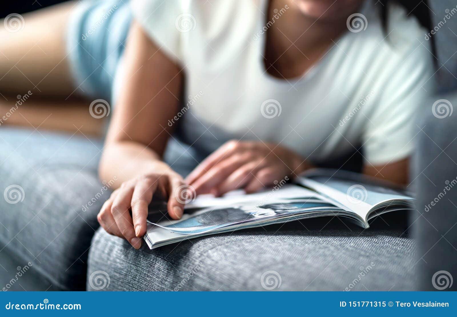 Mujer que miente en el sofá y que lee una revista de la moda o de la belleza Señora que disfruta de su día libre con noticias del
