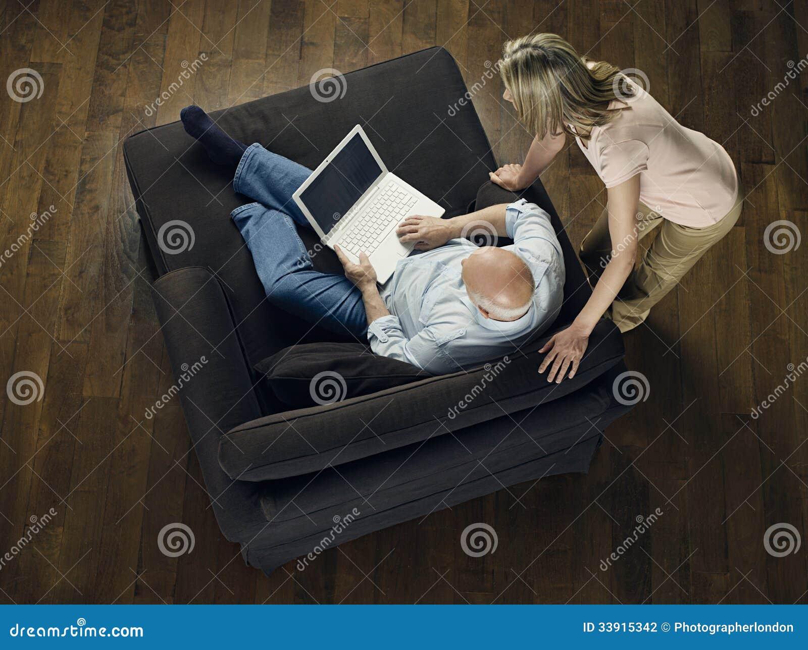 Mujer que mira el ordenador portátil calvo del uso del hombre