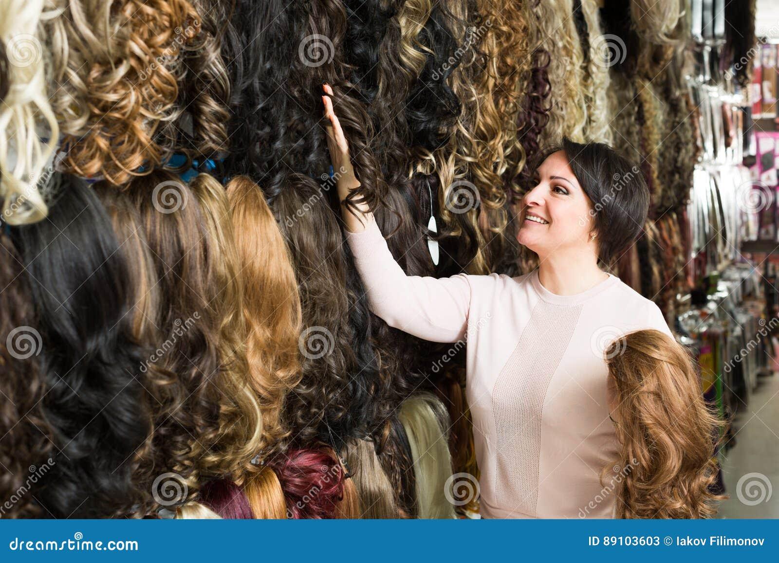 Mujer que mira extensiones del pelo del color