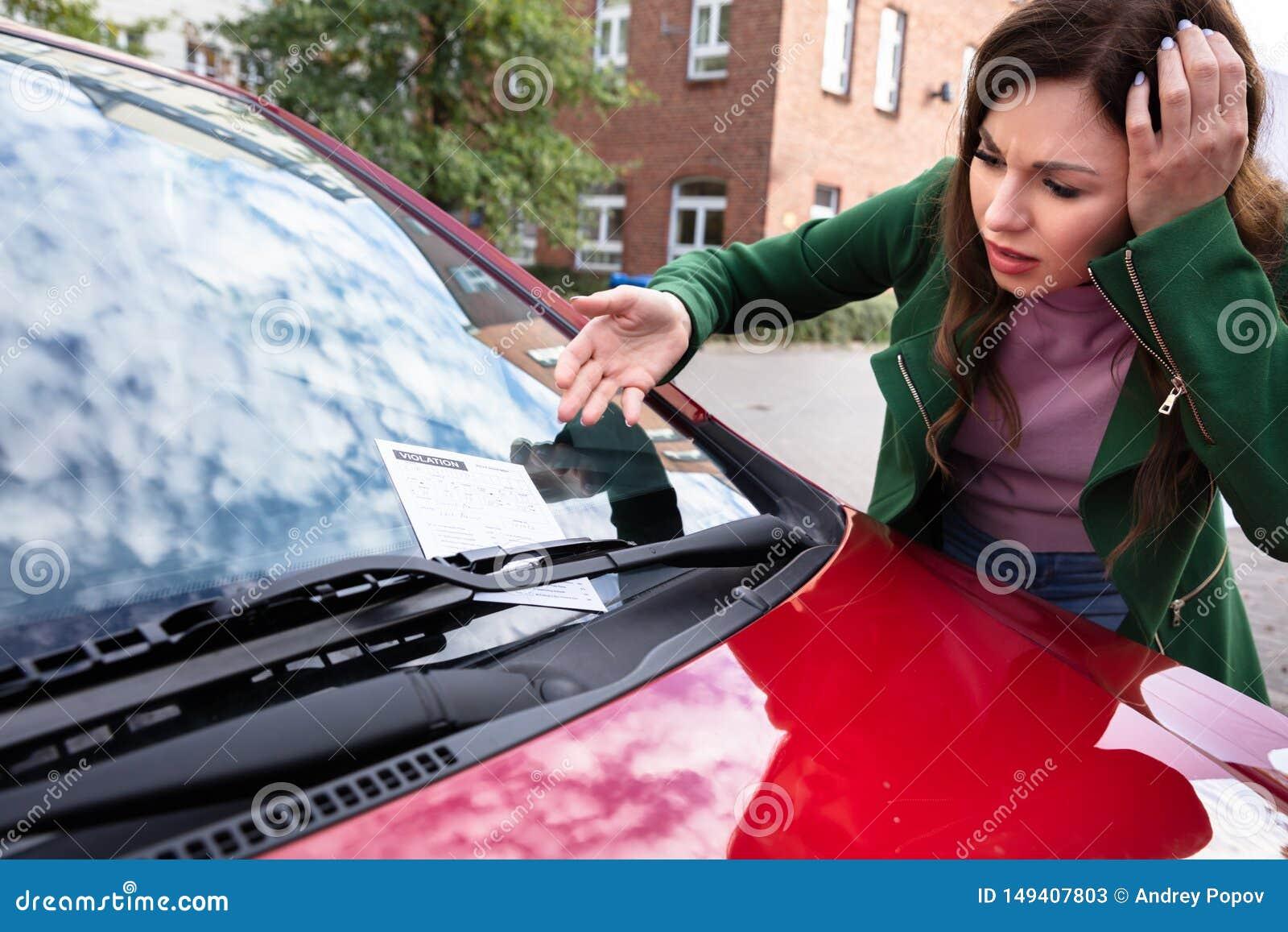 Mujer que mira la multa del boleto para la violaci?n del aparcamiento en el coche