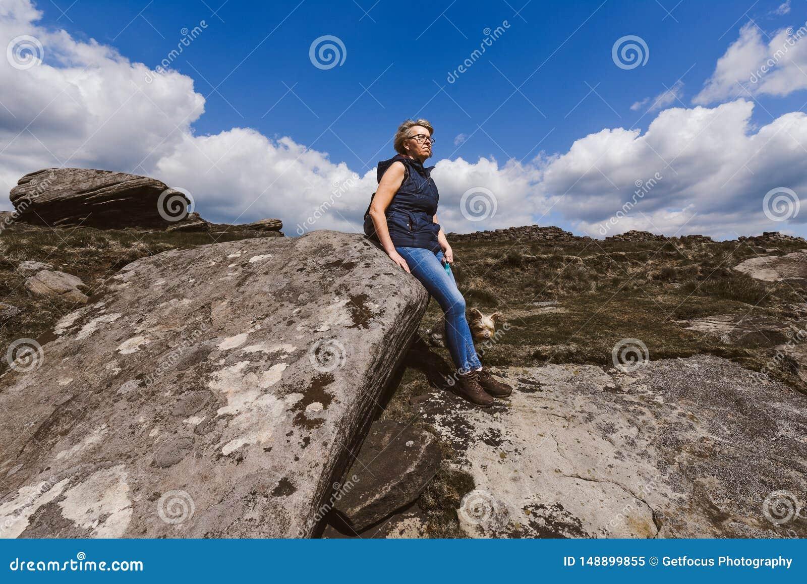 Mujer que mira la visi?n en las rocas de Derbyshire