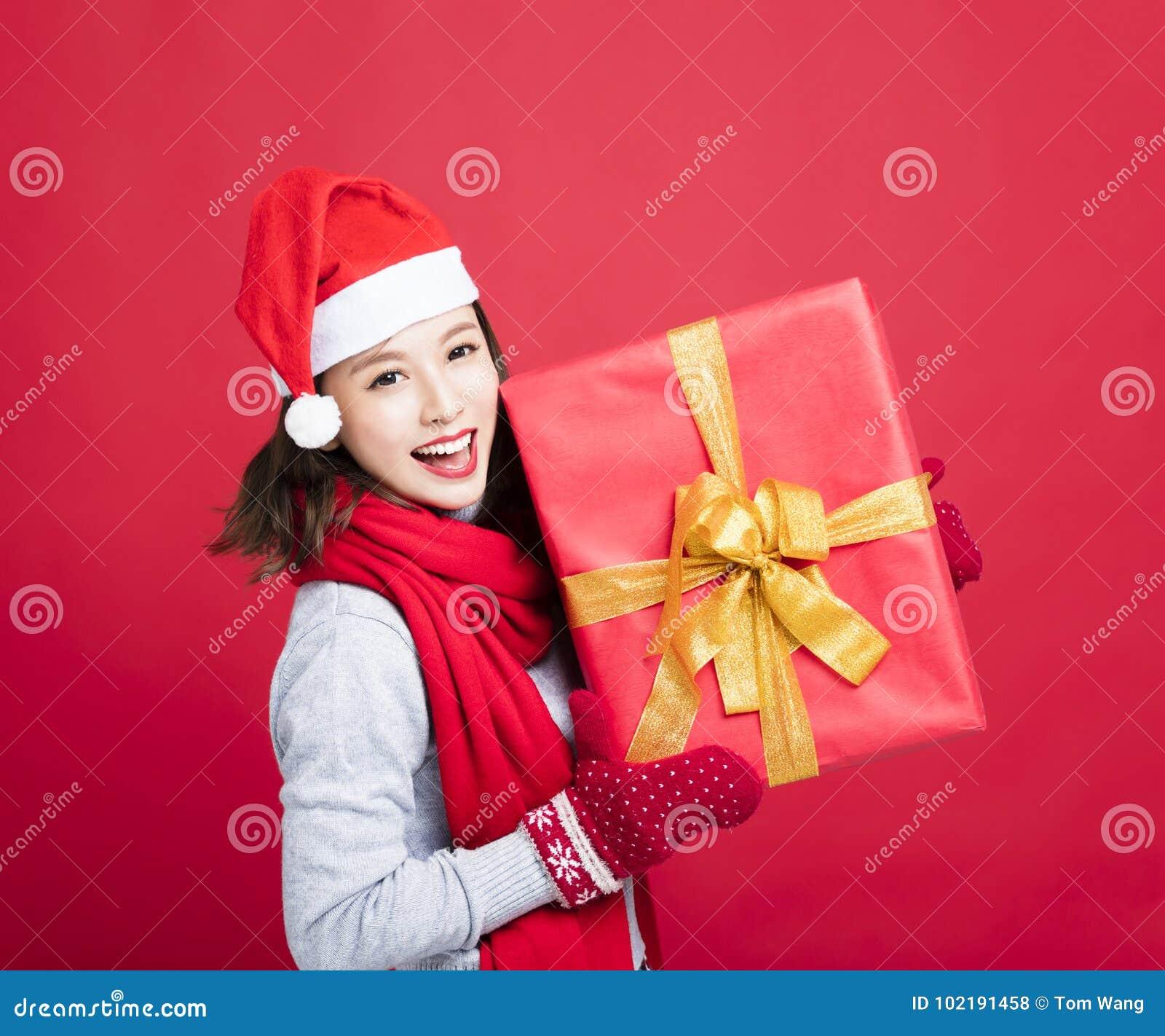 Mujer que muestra la caja de regalo de la Navidad