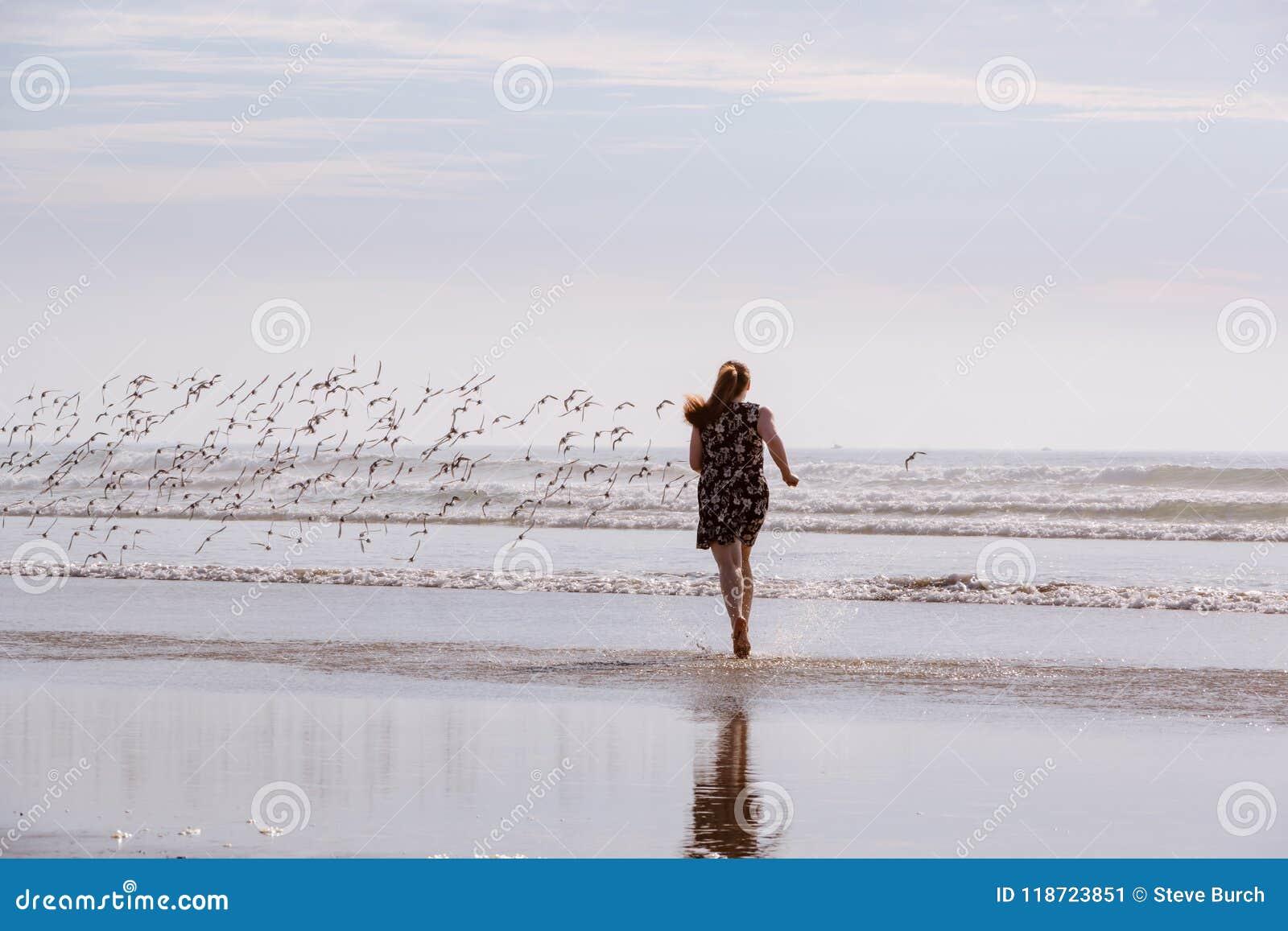 Mujer que persigue pájaros en la playa