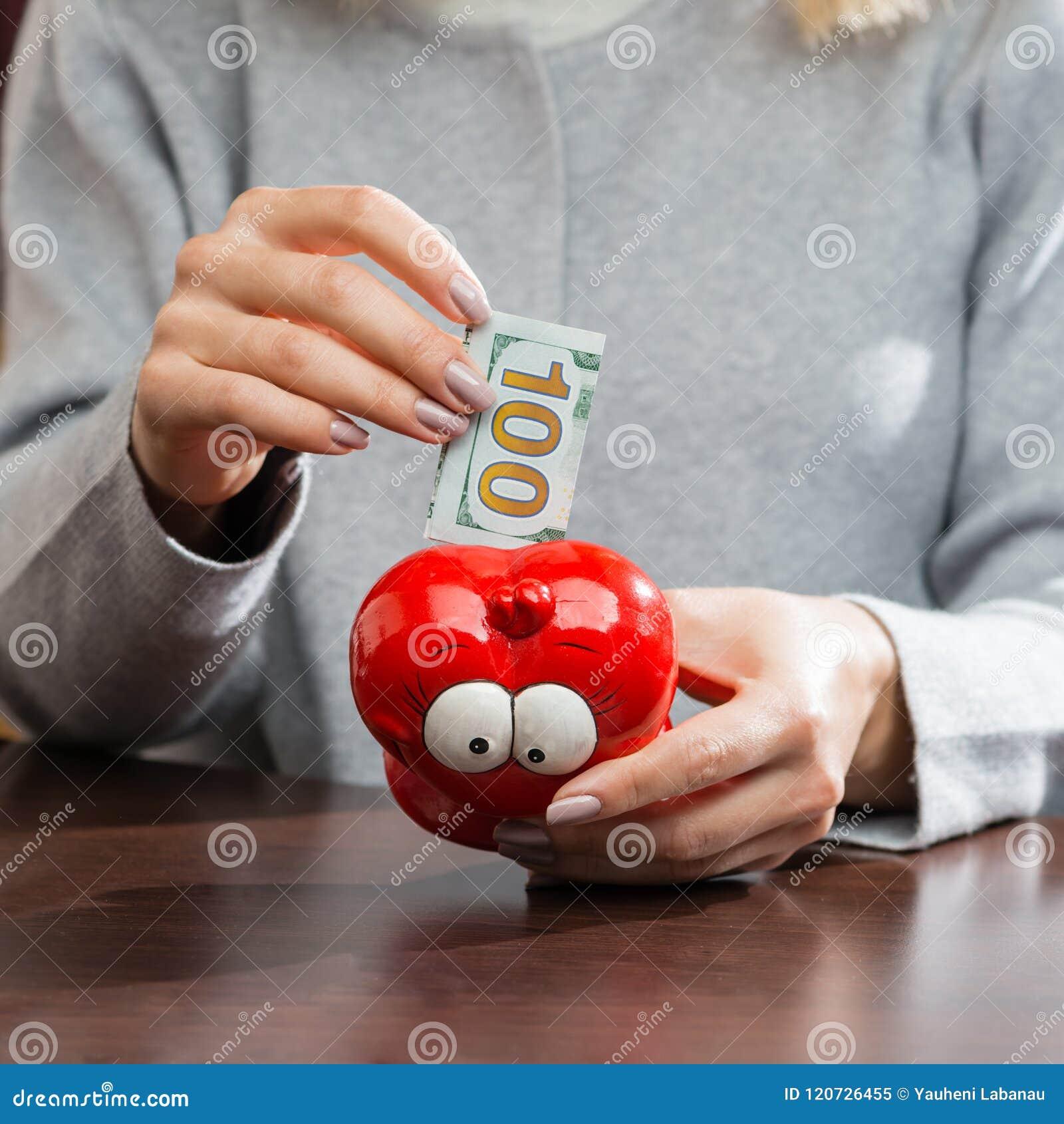 Mujer que pone cientos billetes de banco del euro en un moneybox rojo divertido
