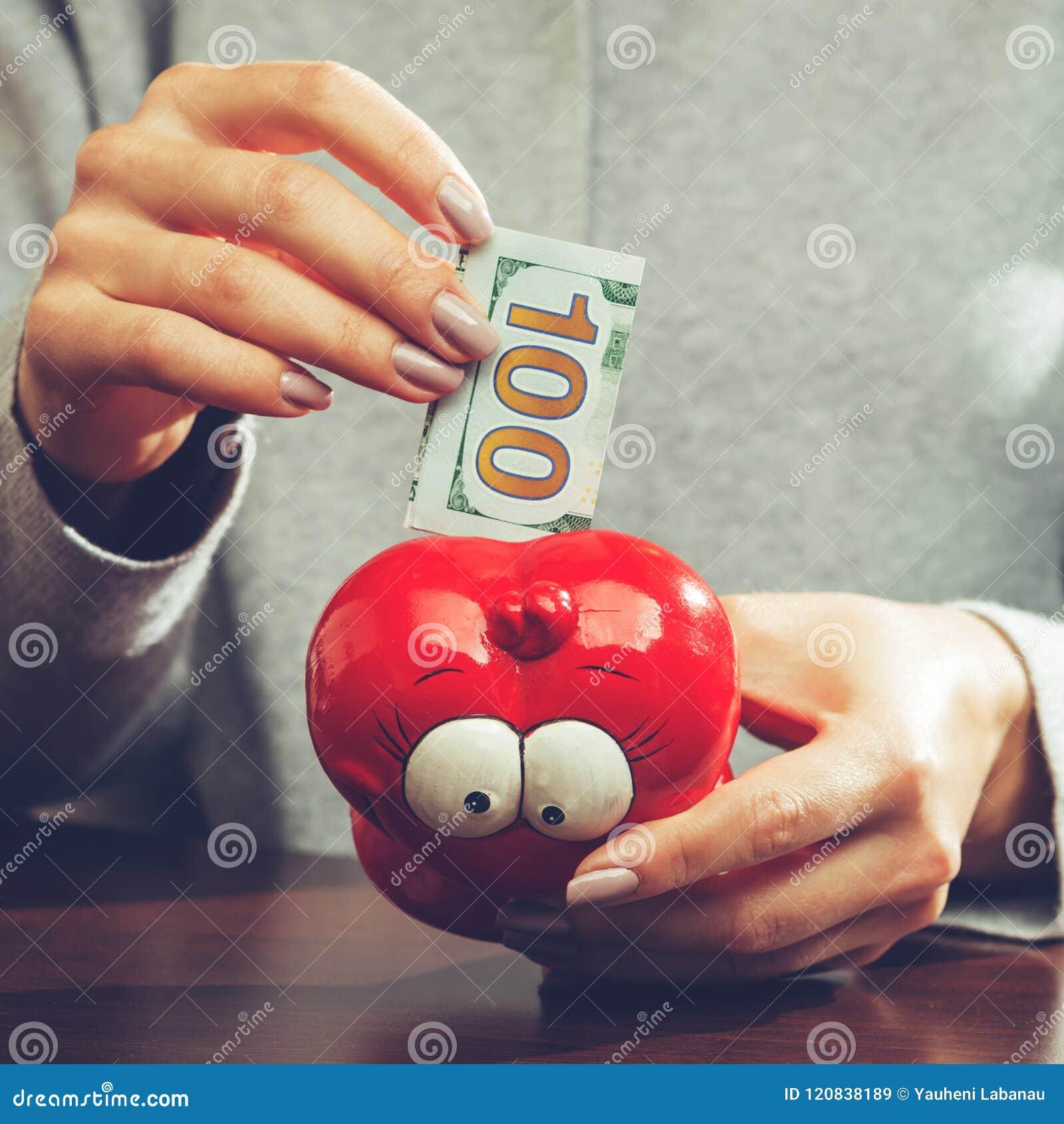 Mujer que pone cientos billetes de banco del euro en un moneybox rojo divertido,