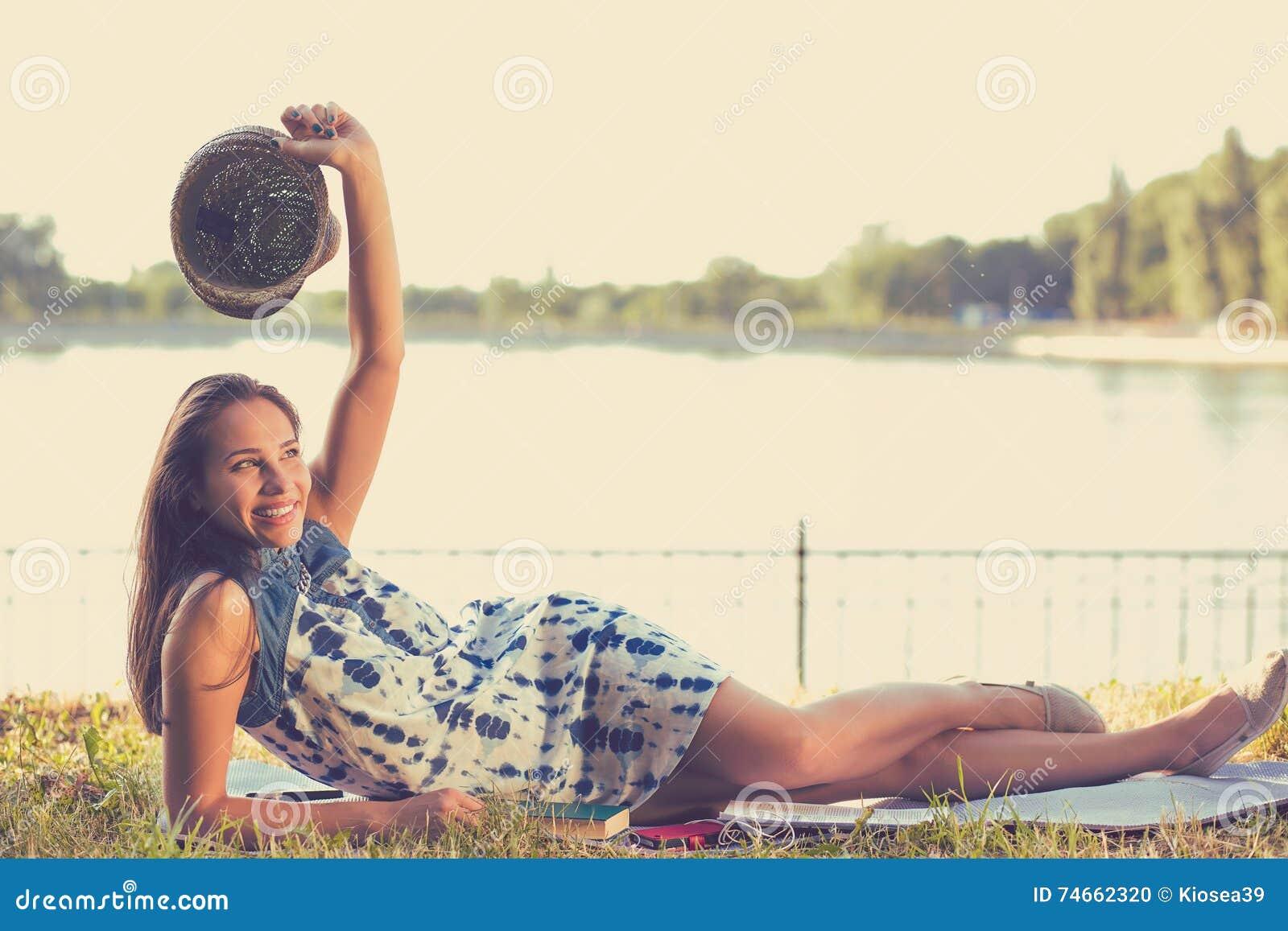 Mujer que pone en un prado delante de un lago