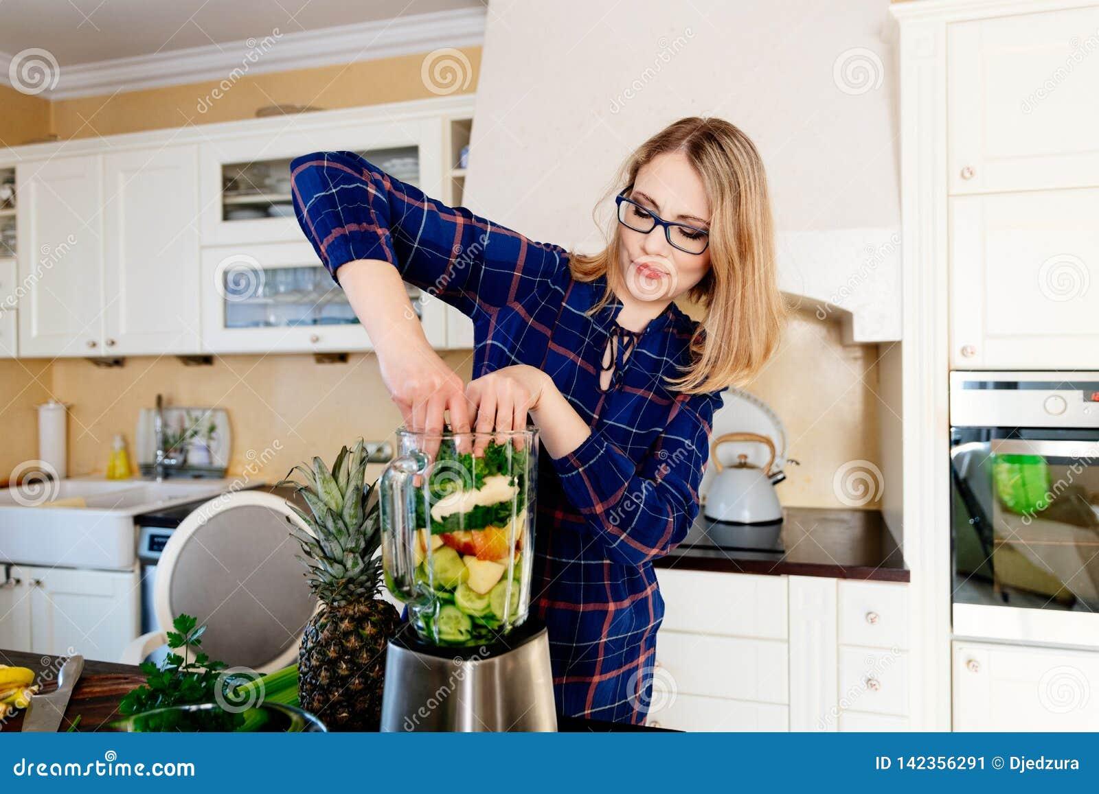 Mujer que pone las frutas y verduras en la licuadora eletrical