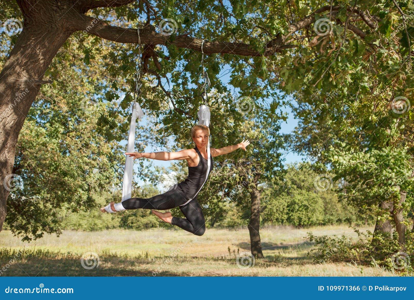 Mujer que practica yoga antigravedad en el árbol cerca del río