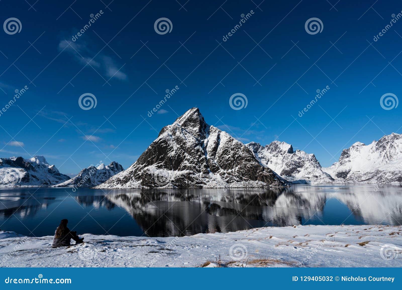 Mujer que presenta en las montañas de las islas de Lofoten Reine, Noruega