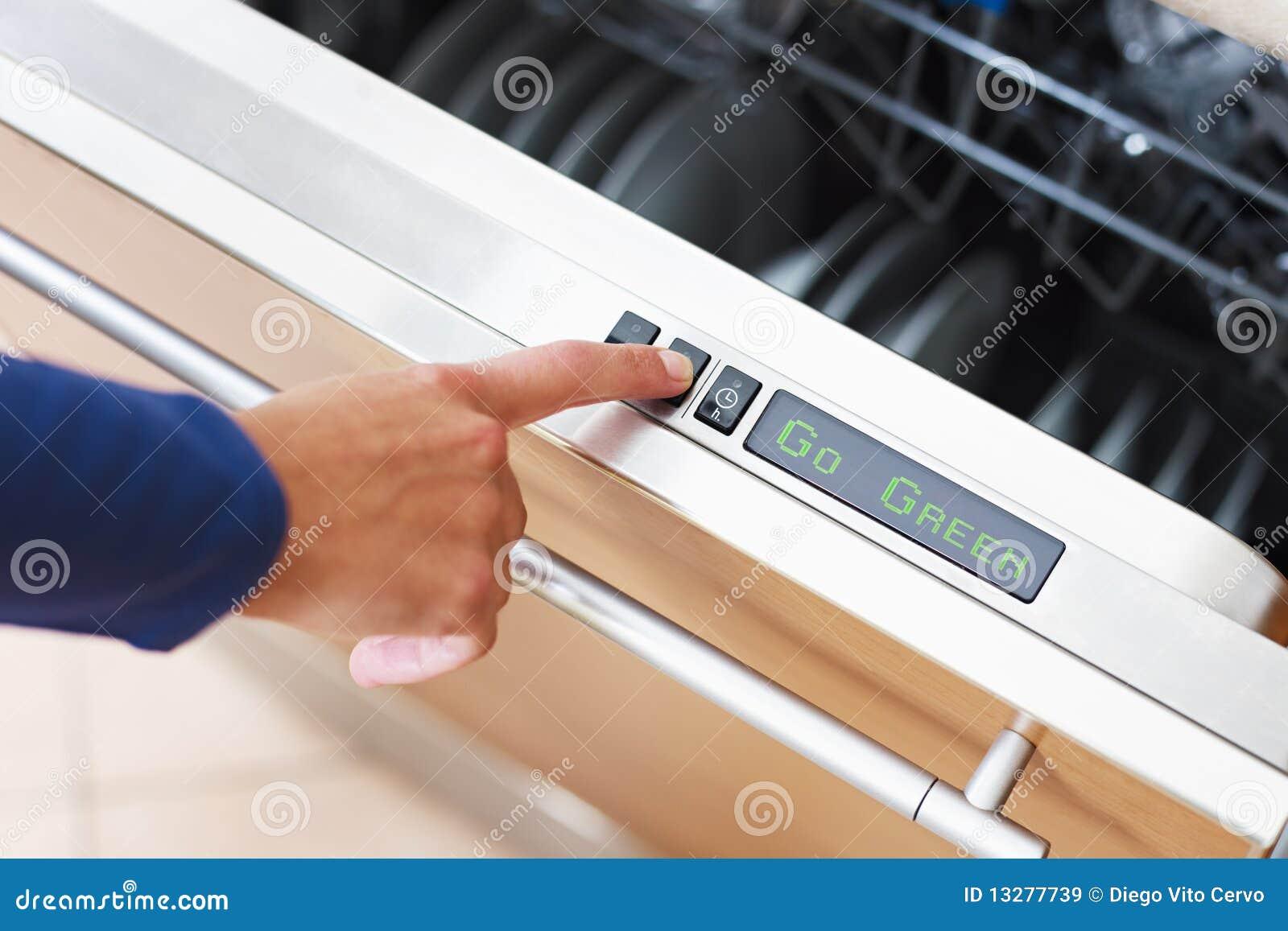 Mujer que presiona el botón del ahorrador de energía en el lavaplatos