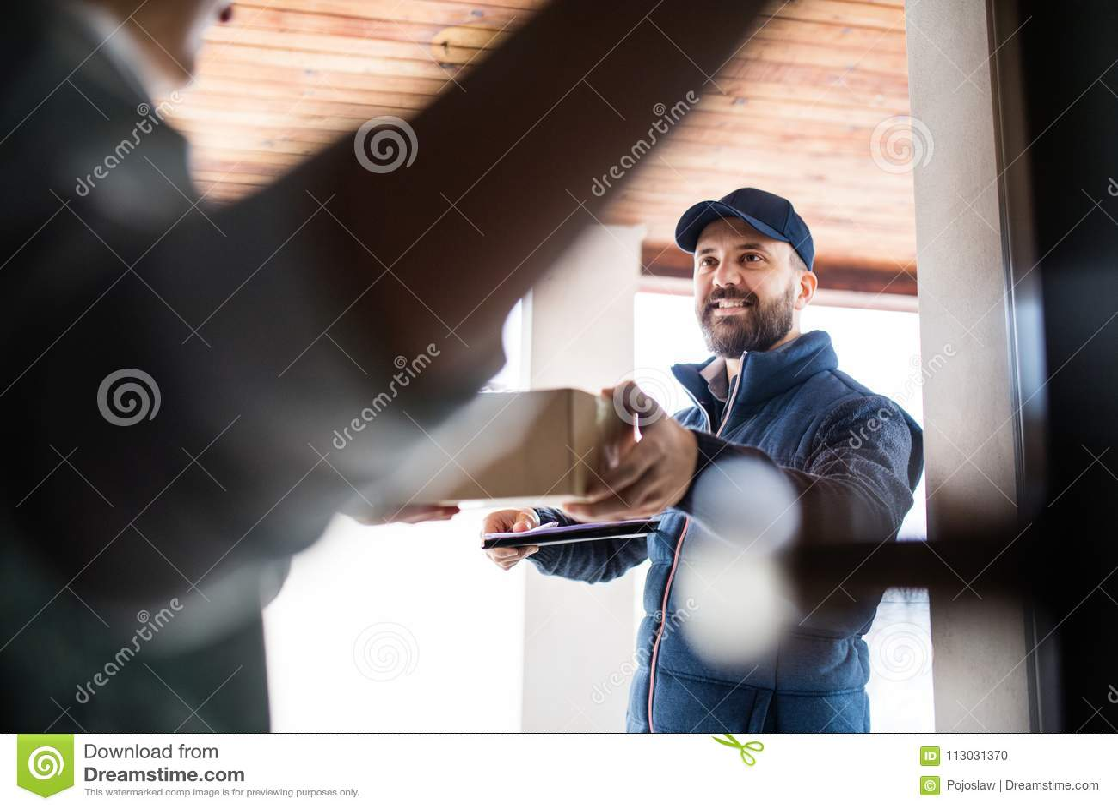 Mujer que recibe el paquete de hombre de entrega en la puerta