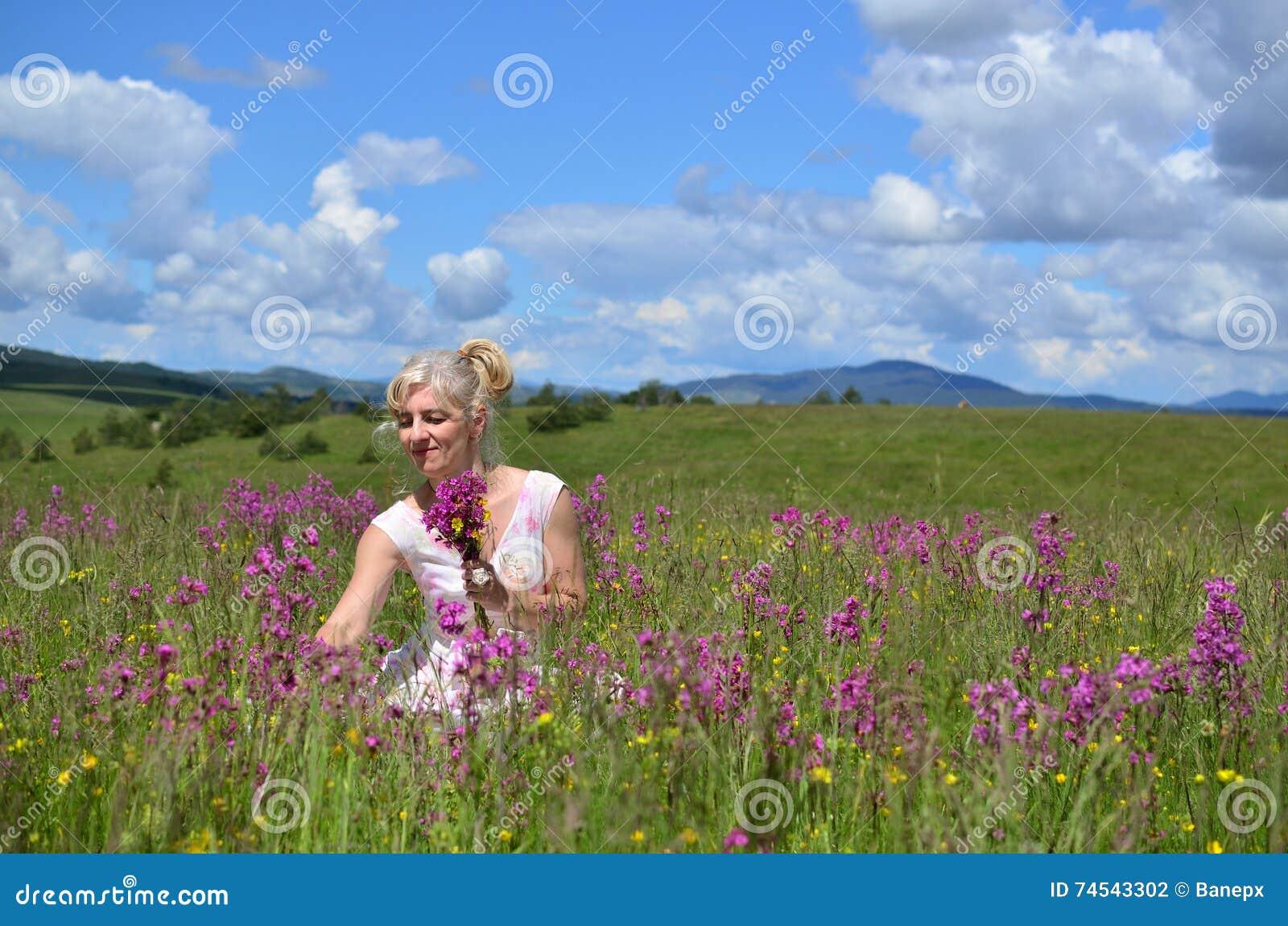 Mujer que recolecta las flores en prado del verano