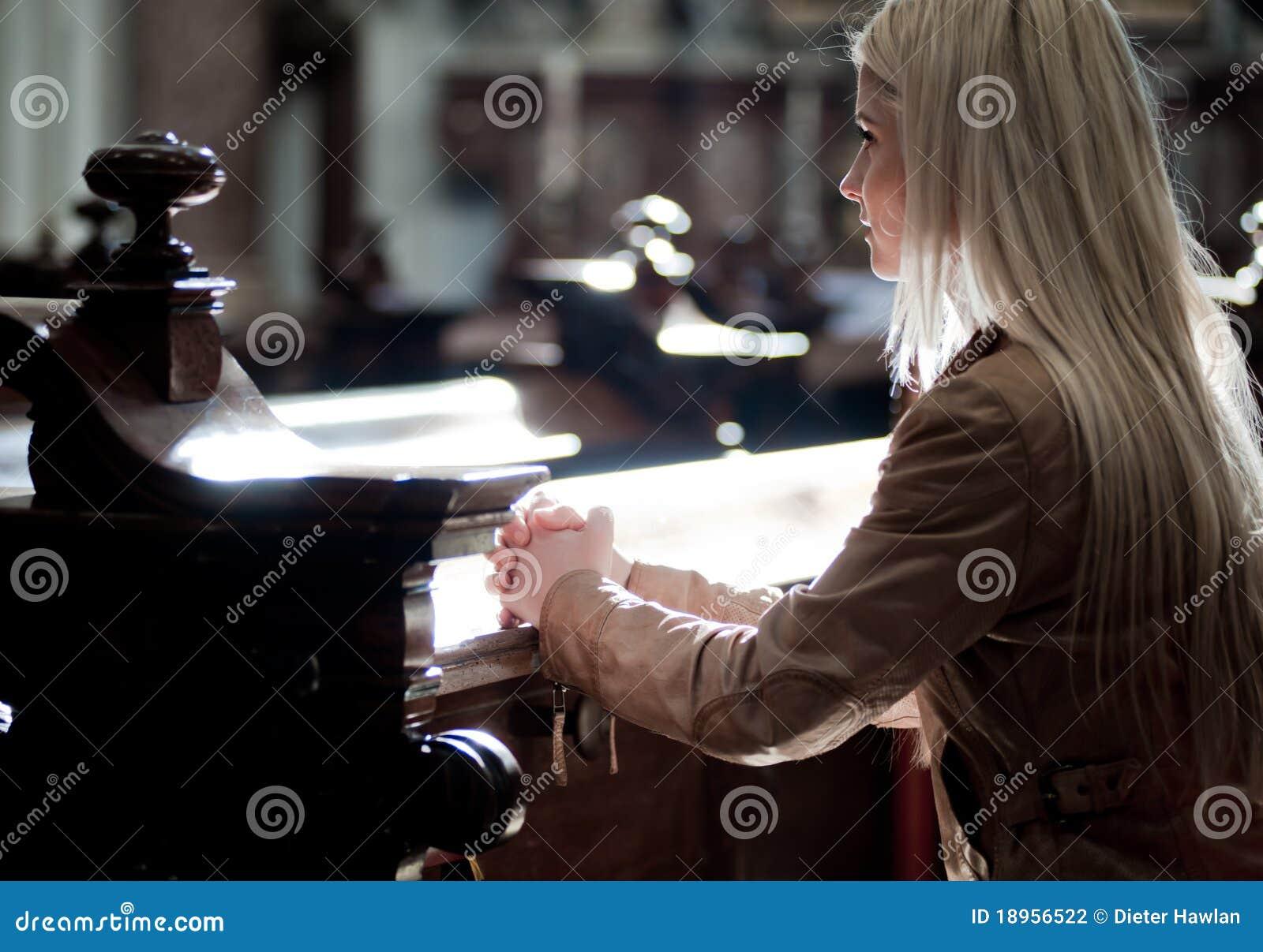 Mujer que ruega en la iglesia