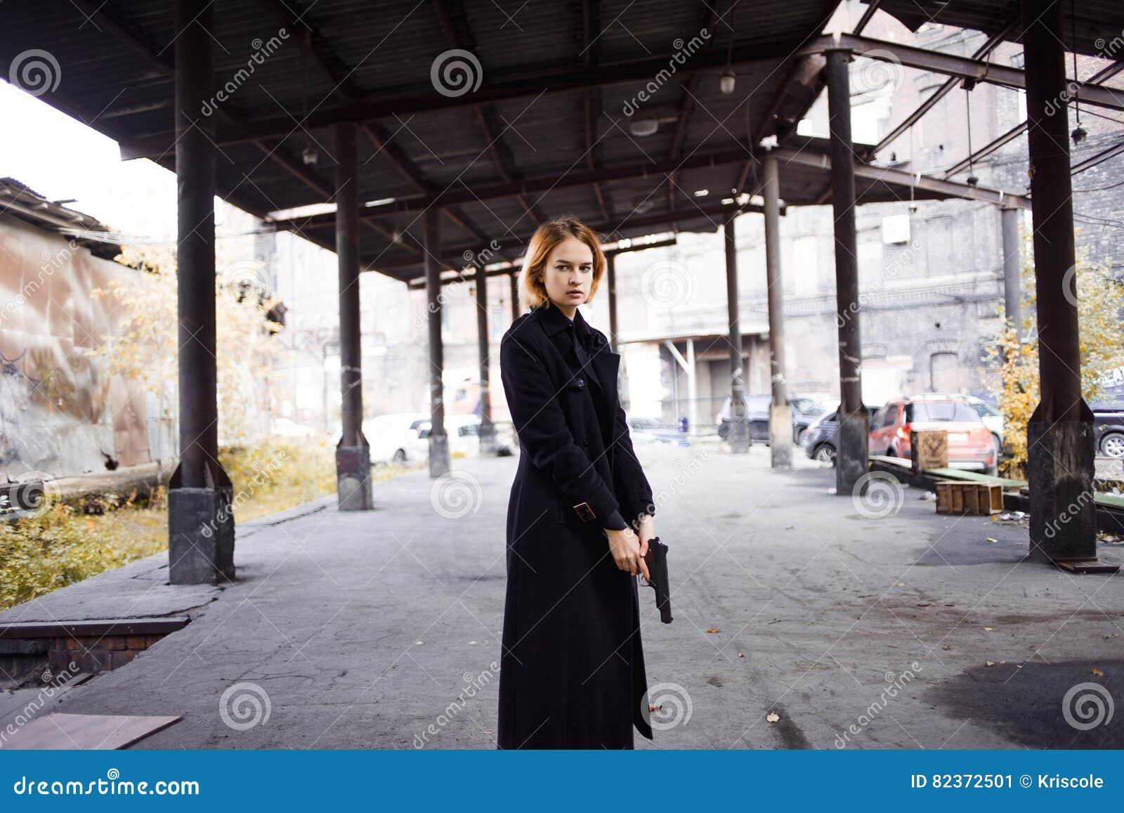 Mujer que señala un arma Tiroteo de la muchacha de la mafia en alguien en la calle