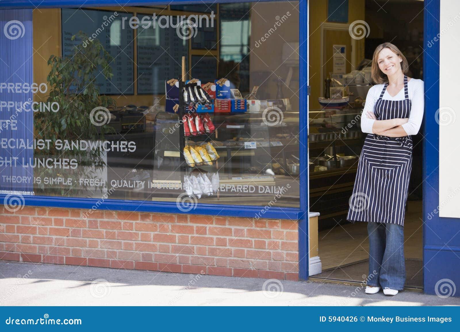 Mujer que se coloca en el umbral de la sonrisa del restaurante