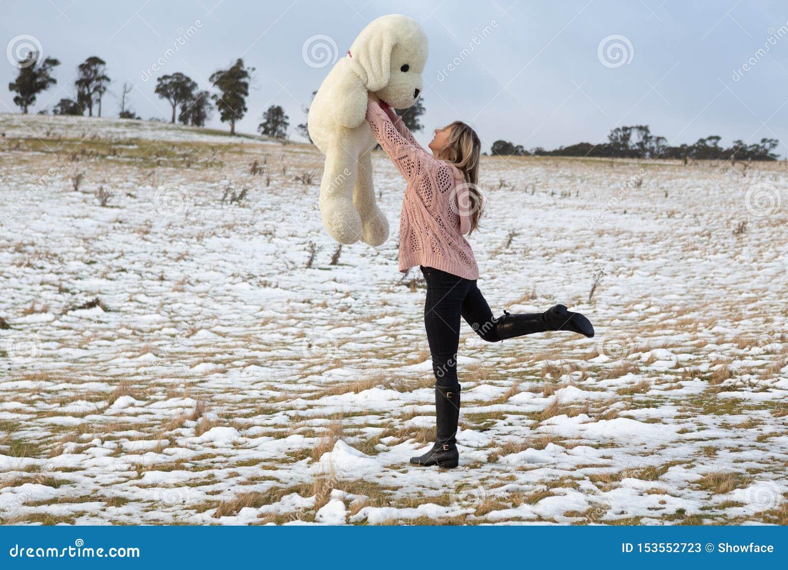 Mujer que se divierte en la nieve con el oso de peluche