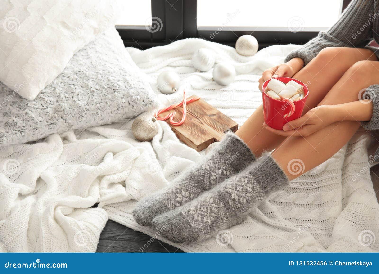 Mujer que se relaja con la taza de bebida caliente del invierno en la tela escocesa hecha punto