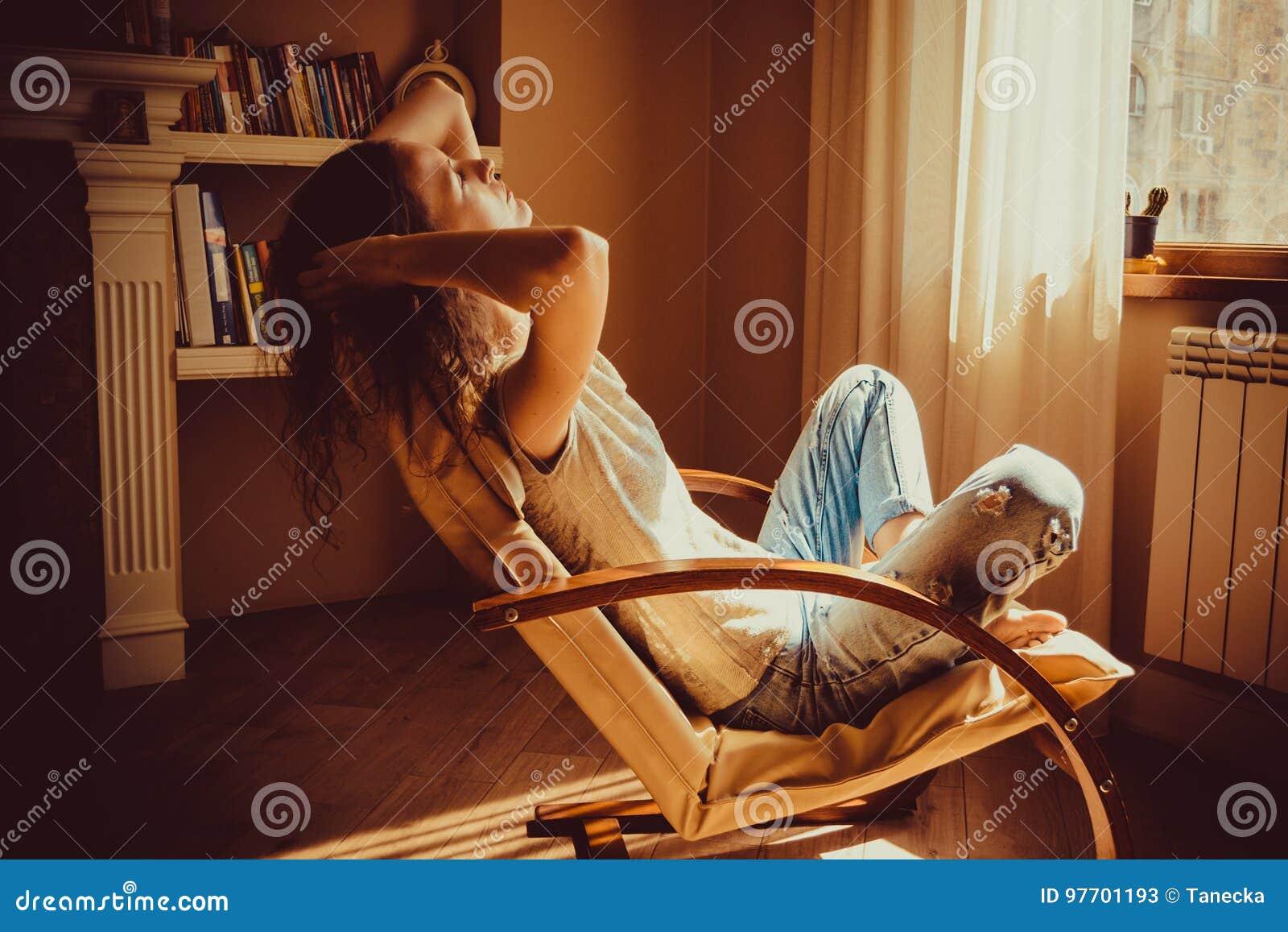 Mujer que se relaja después de trabajo en silla moderna cómoda cerca de ventana en sala de estar Luz natural caliente Hogar acoge