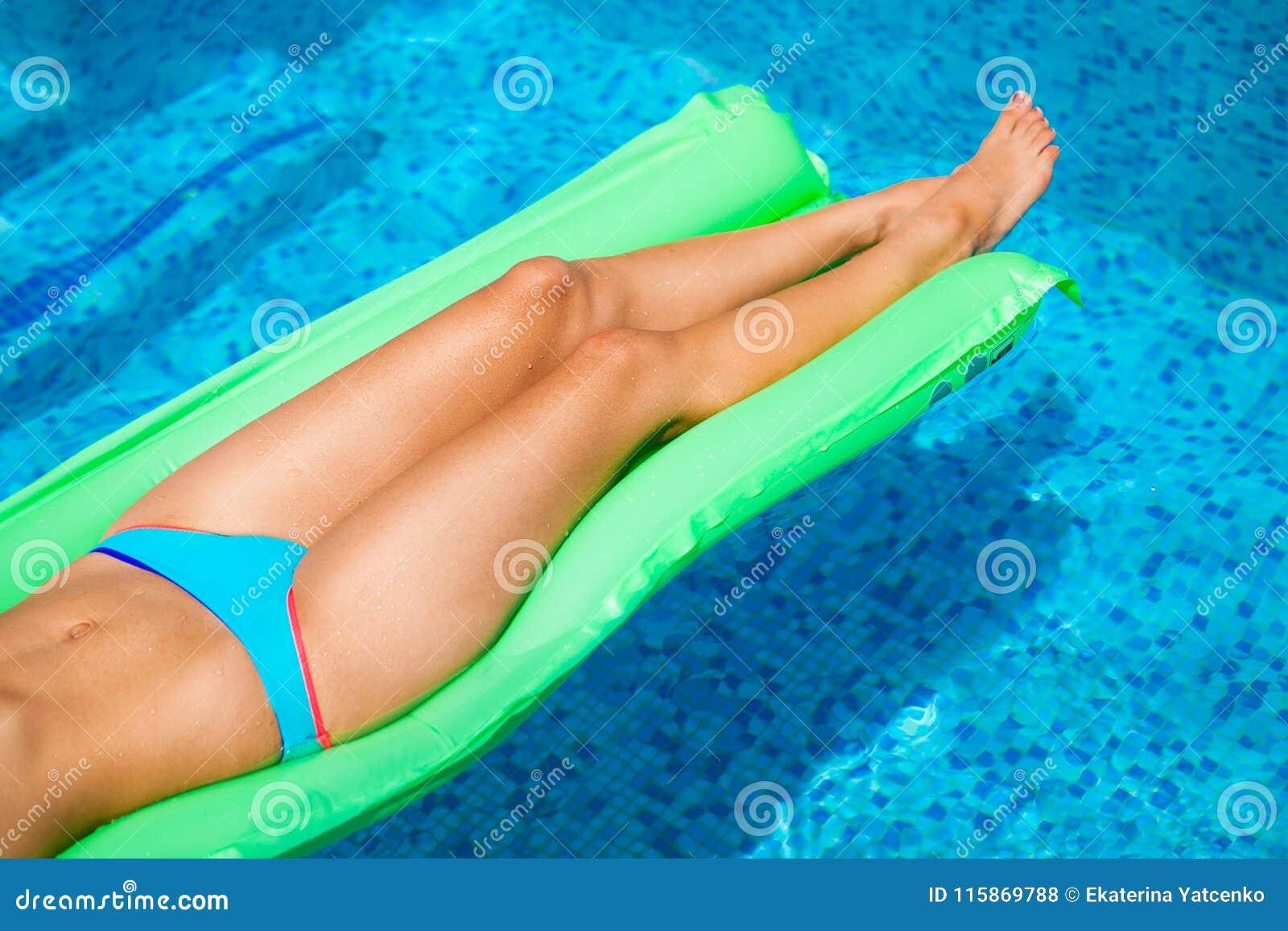 Mujer que se relaja en el colchón en el agua de la piscina en día soleado caliente S