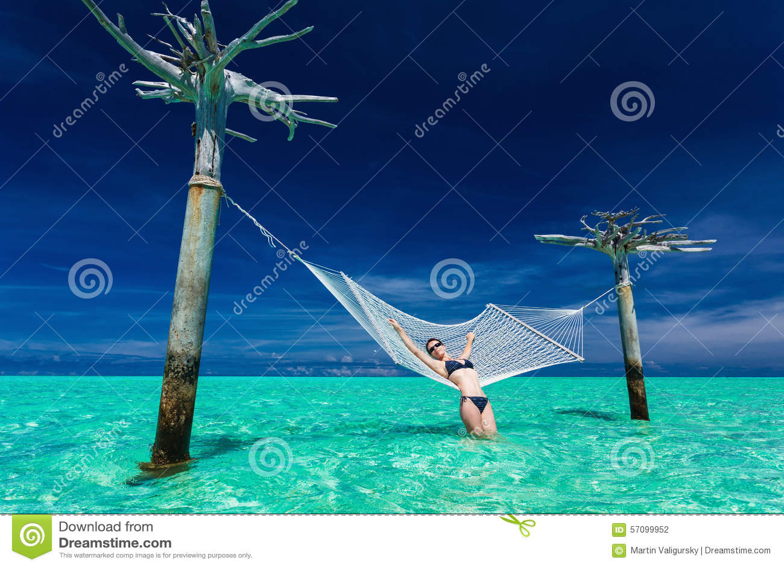 Mujer que se relaja en la hamaca del sobre-agua en el medio de l tropical