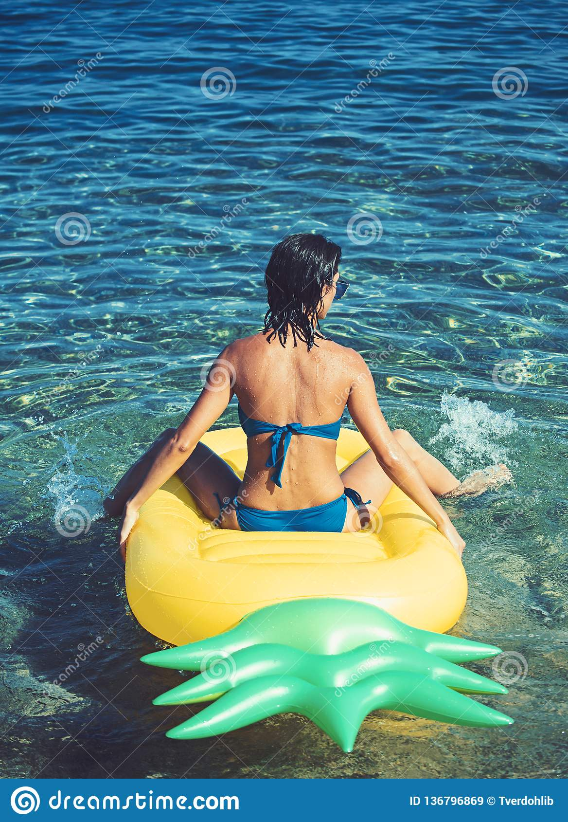 Mujer que se relaja en una agua de la piscina o de mar