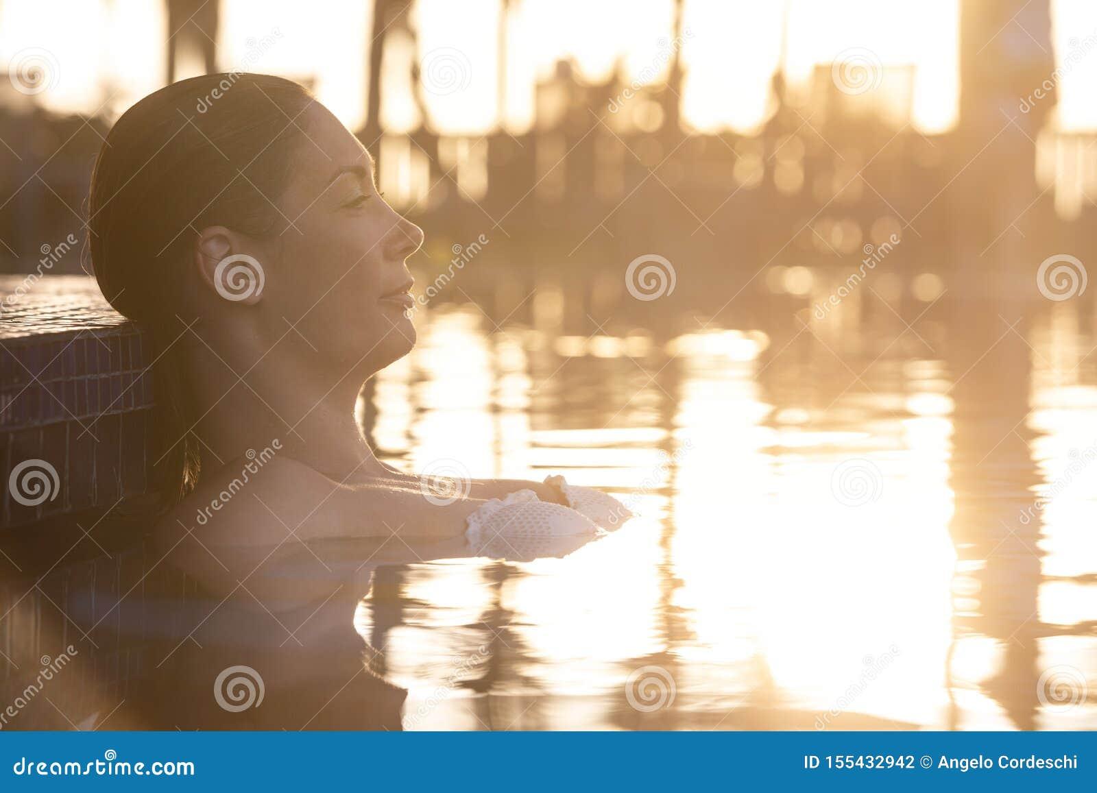 Mujer que se relaja por la piscina en la puesta del sol