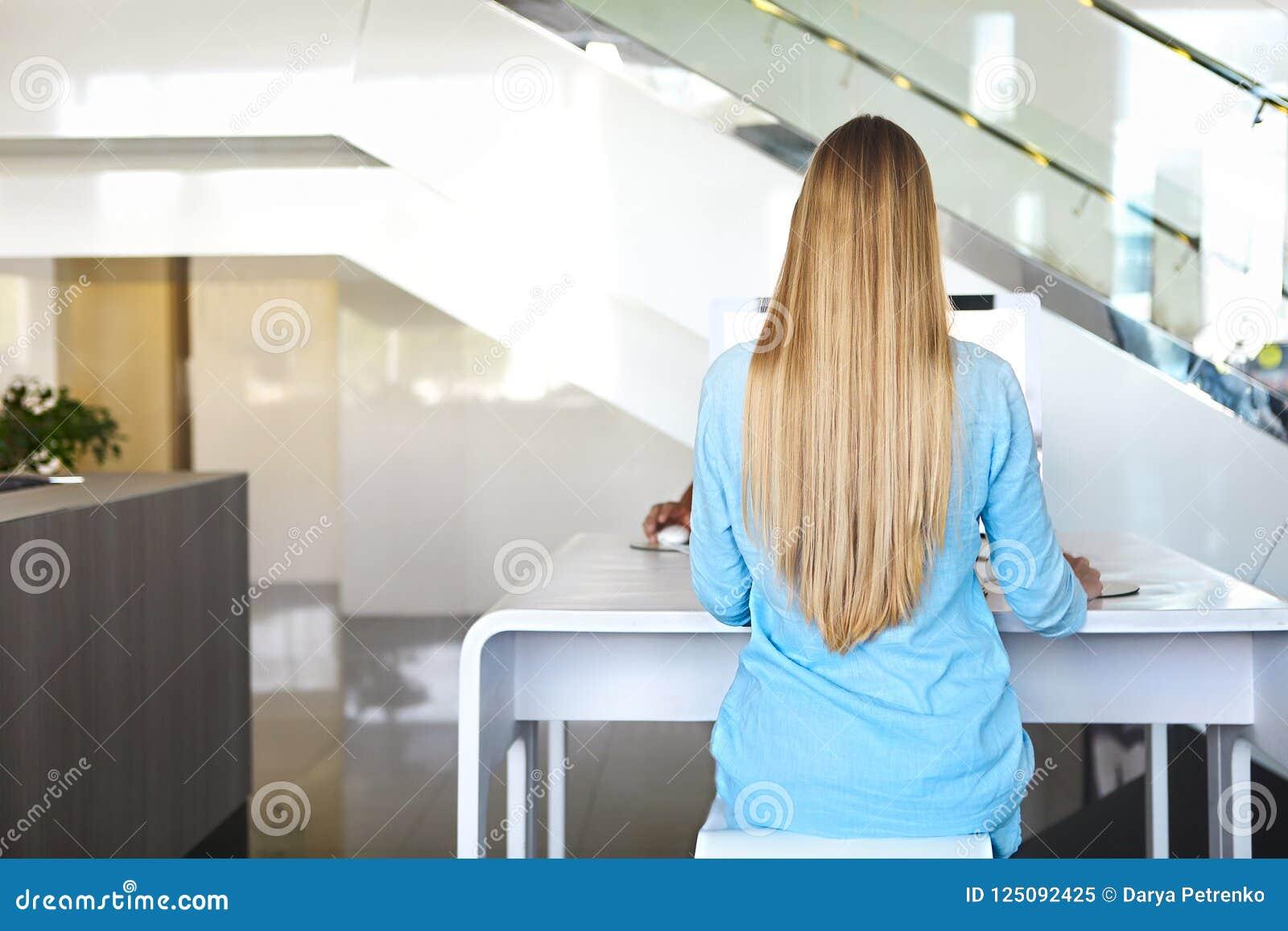 Mujer que se sienta cómodamente en la tabla por el ordenador Visión trasera