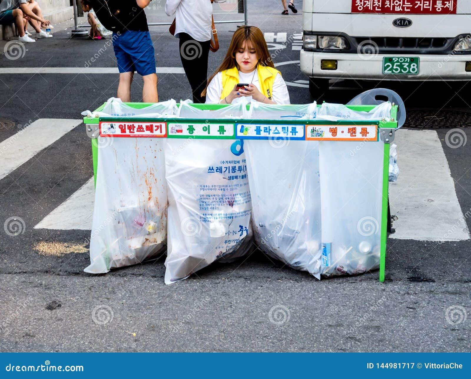 Mujer que se sienta cerca de la basura que clasifica los envases con las inscripciones coloreadas para las botellas plásticas, d