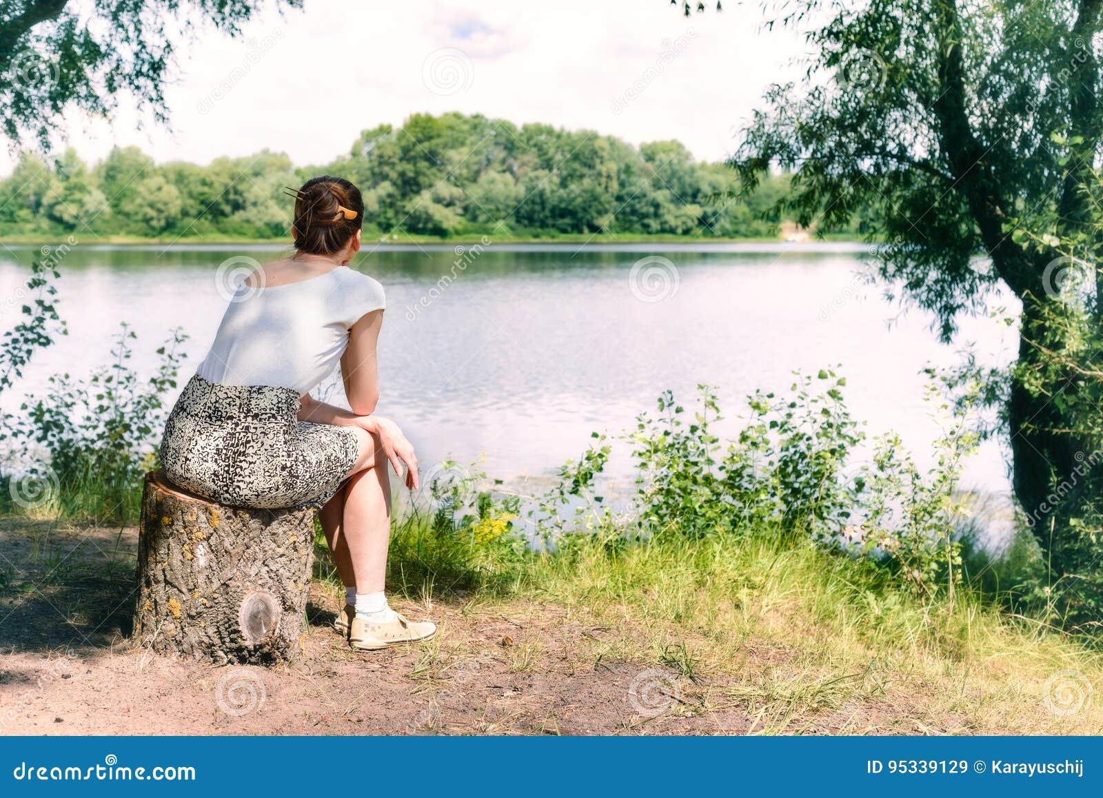 Mujer que se sienta cerca del río
