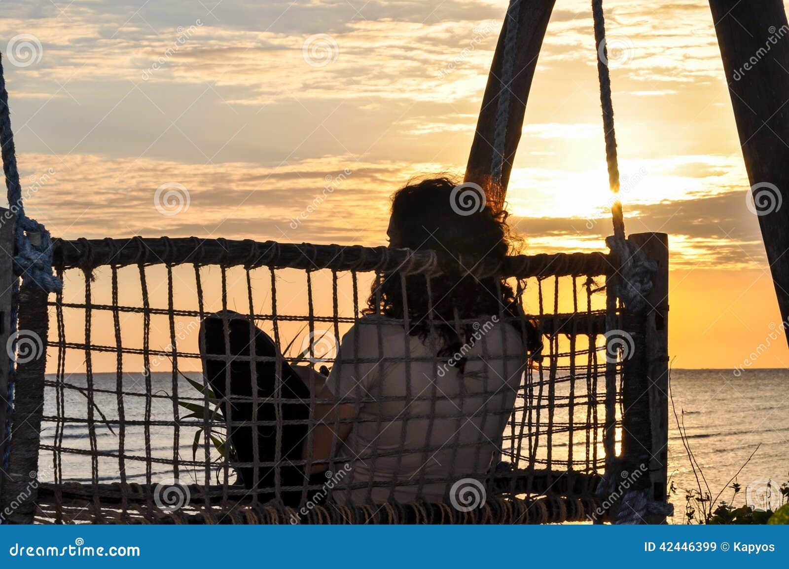 Mujer que se sienta con el fondo de la puesta del sol