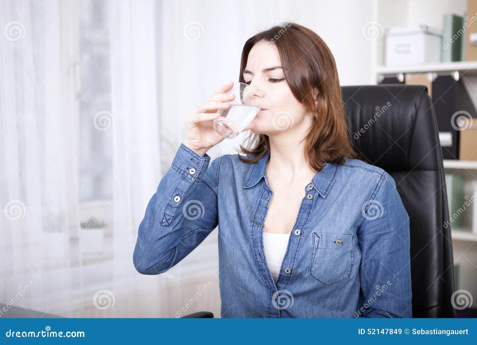 Mujer que se sienta en el agua potable de la silla de la oficina