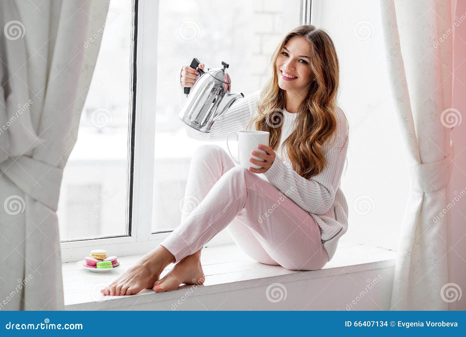 Mujer que se sienta en el alféizar y el té o el café de colada de la caldera