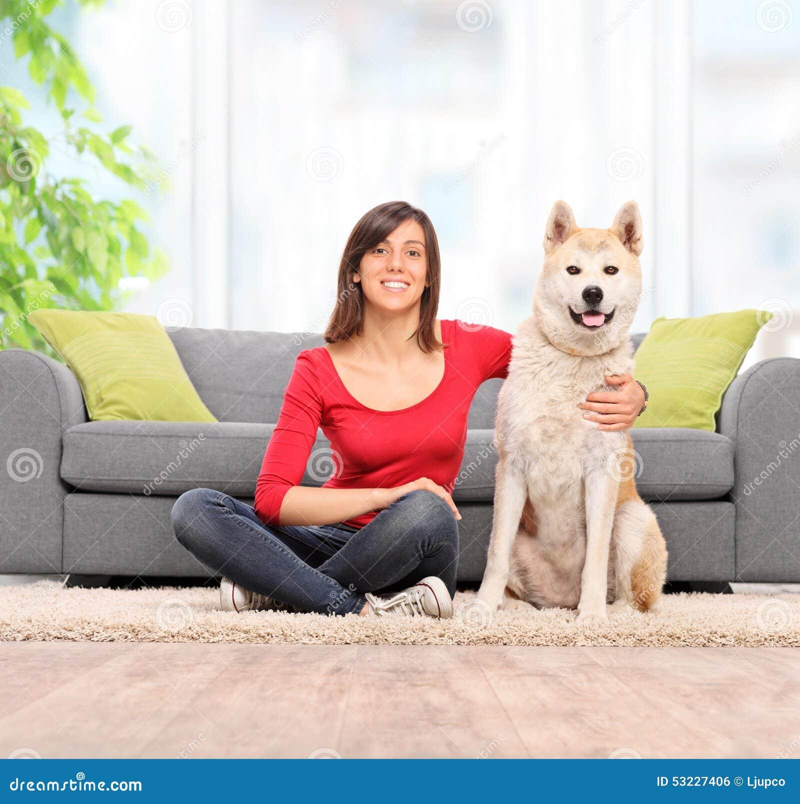 Mujer que se sienta en el piso con su perro casero
