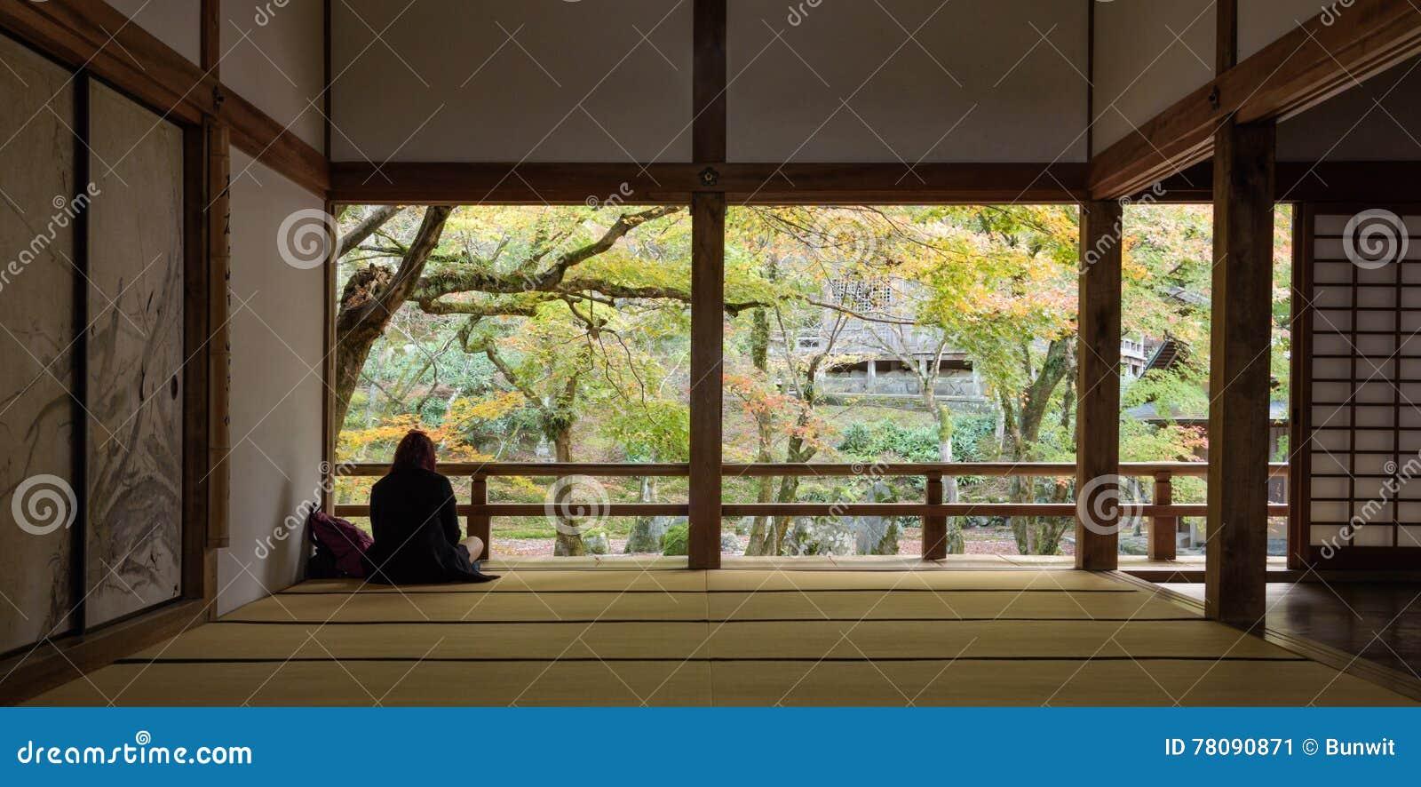 Mujer que se sienta en jardín de piedras de la parte posterior del templo del komyozenji