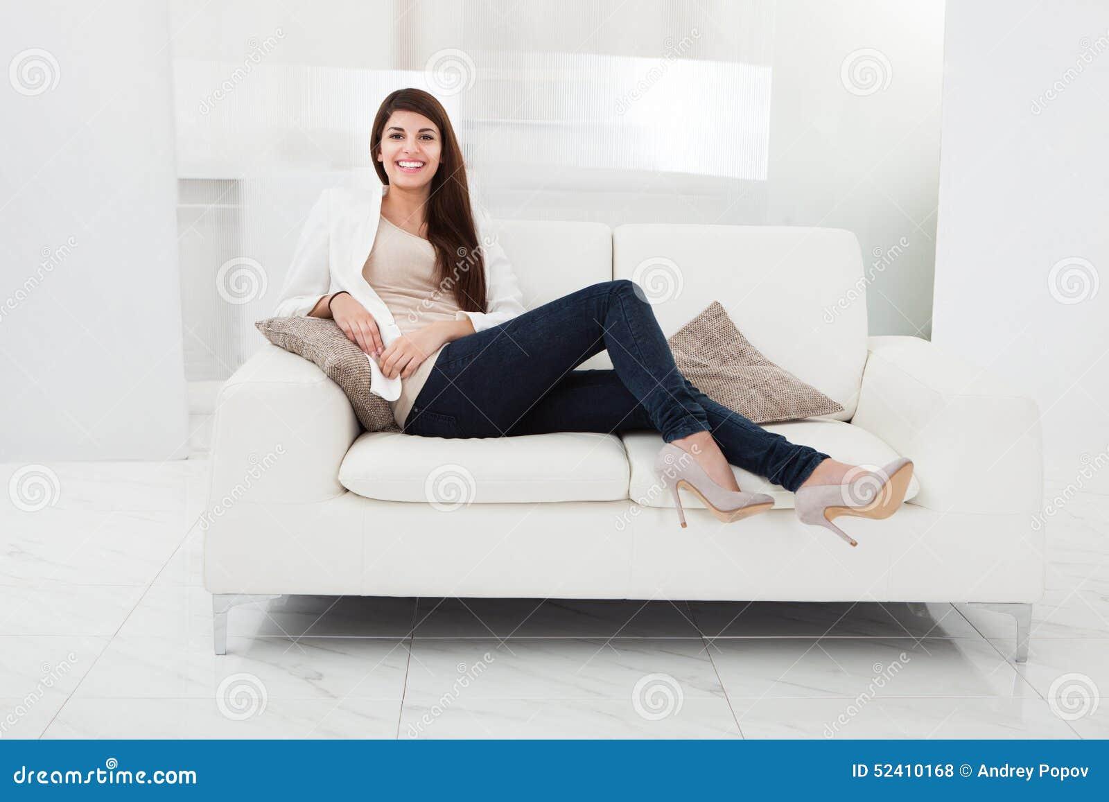 Mujer que se sienta en un sofá