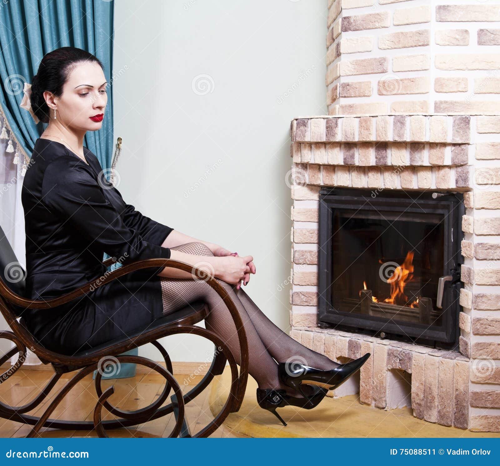 f13bfe703376 Mujer Que Se Sienta En Una Mecedora Delante De Una Chimenea Imagen ...