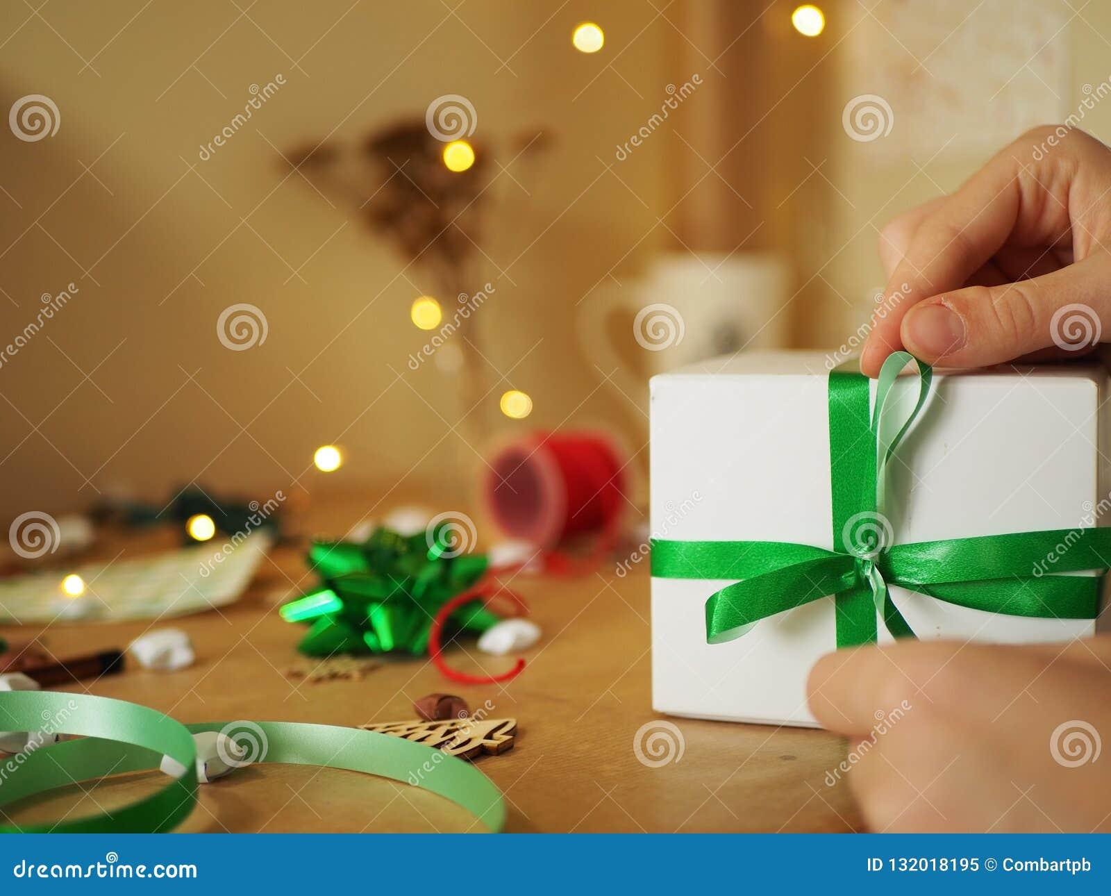 Mujer que sostiene el regalo de la Navidad con la cinta verde